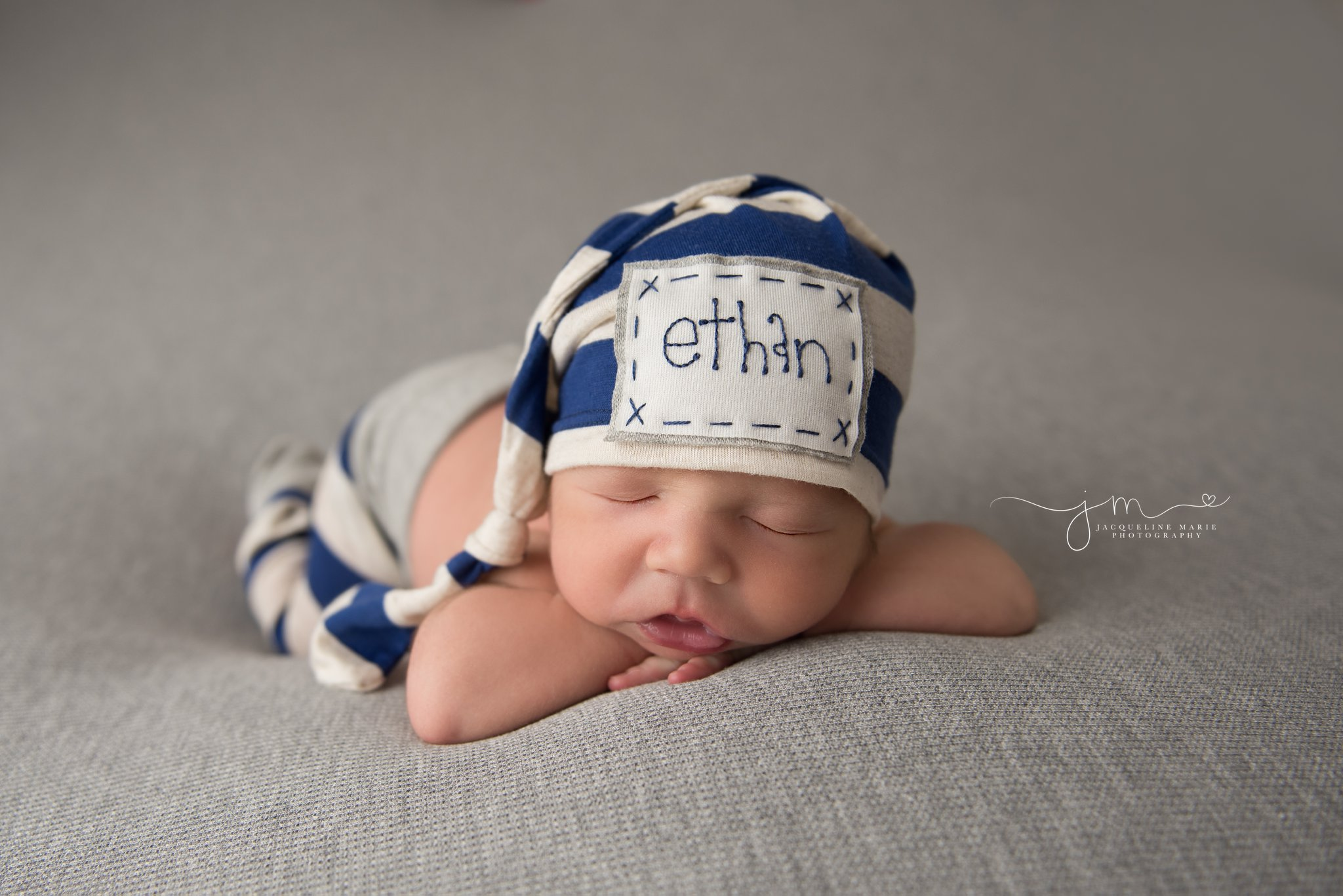 2 week old newborn baby boy wears stripe hat and pants for newborn photography pictures in columbus ohio