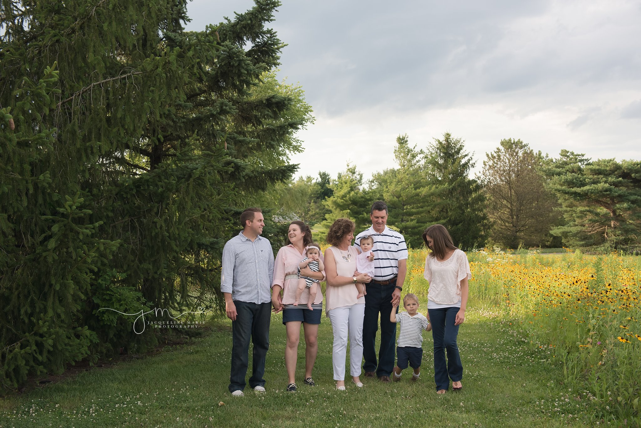 columbus ohio family photographer features family walking and holding hands while smiling in a field of flowers