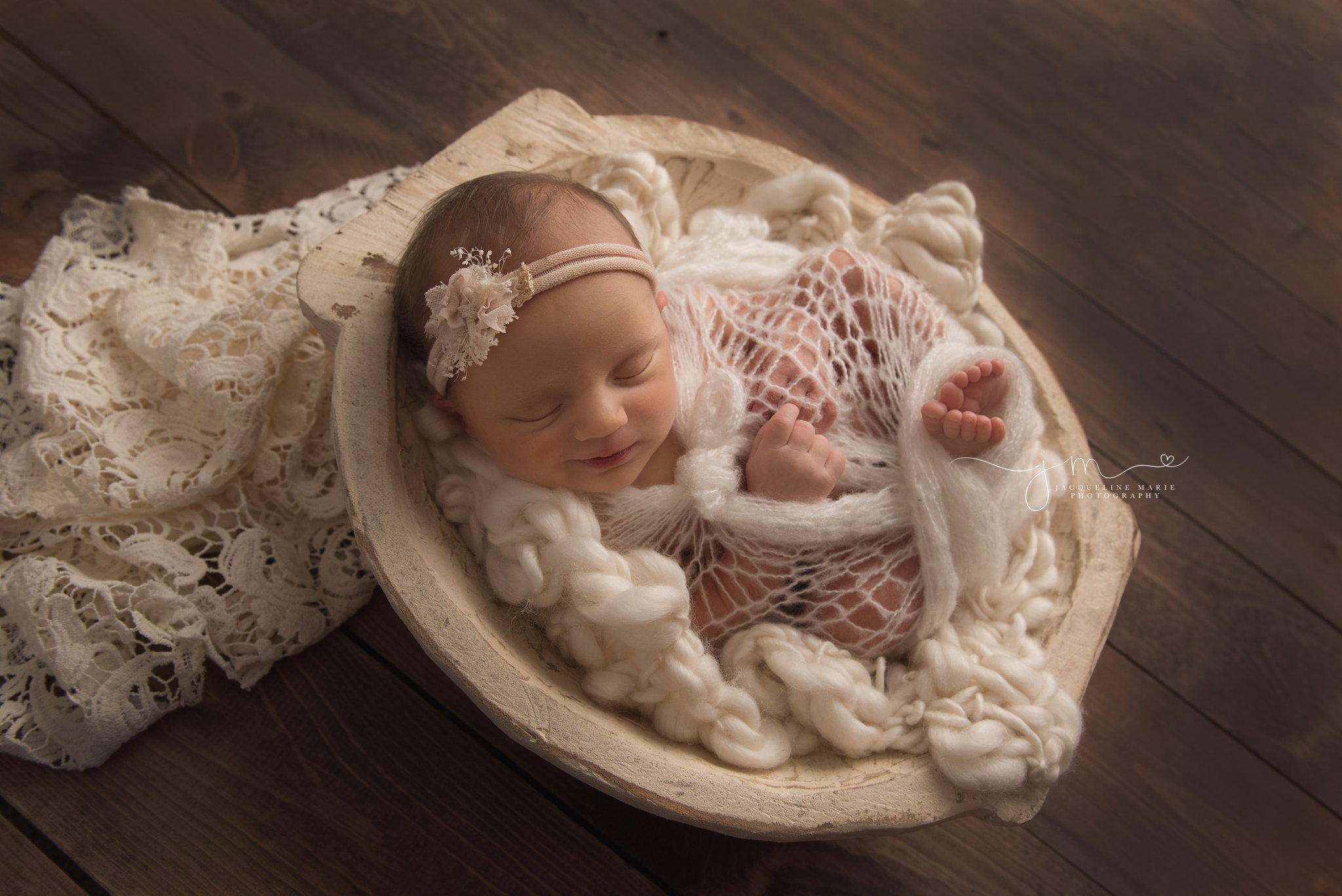 7 day old newborn baby is wrapped in vintage lace for newborn photography pictures in columbus ohio