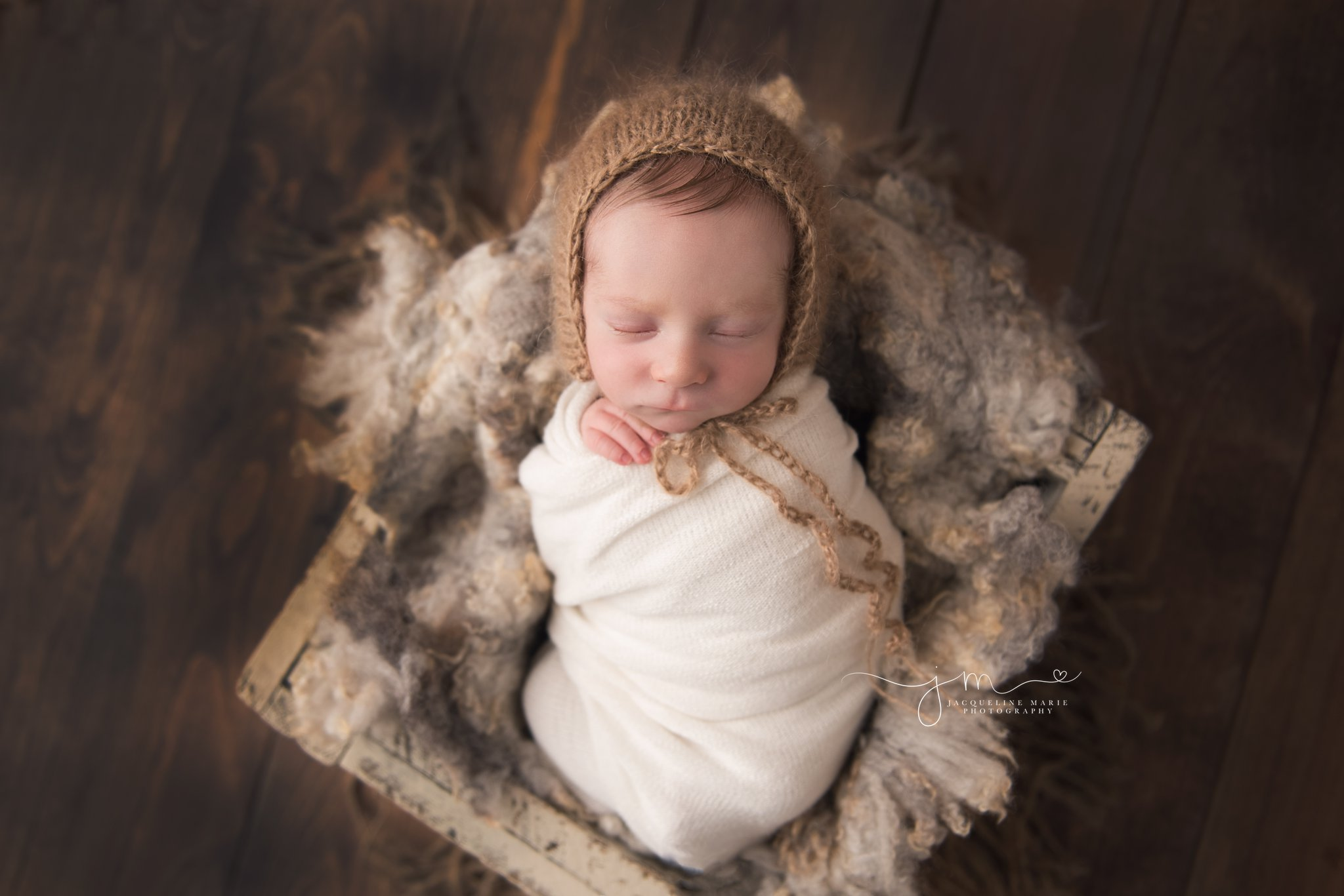 columbus ohio newborn baby boy is swaddled in cream wrap and tan bonnet for newborn pictures at jacqueline marie photography studio