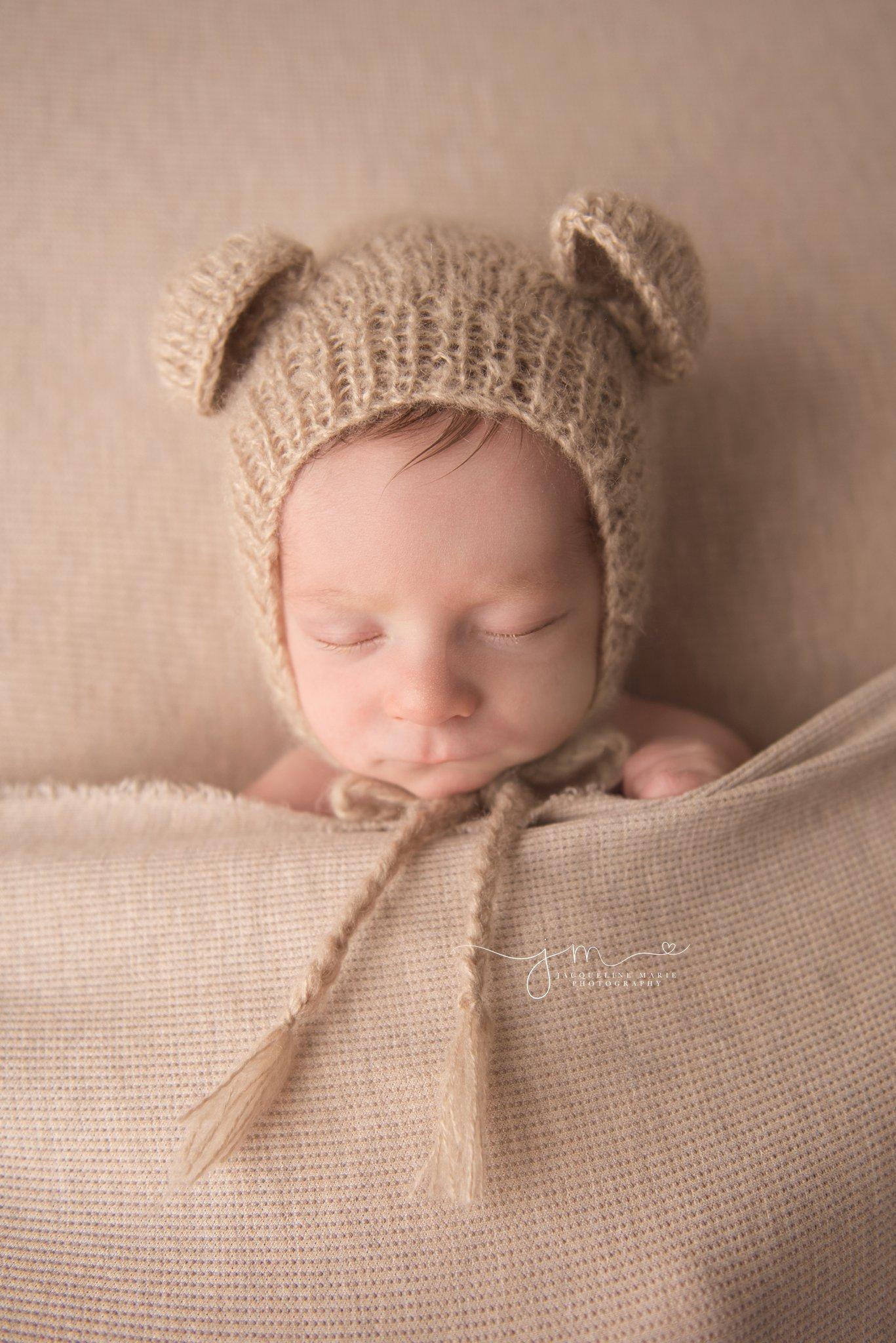 columbus ohio newborn baby features features portraits of baby boy wearing teddy bear bonnet at newborn portrait studio