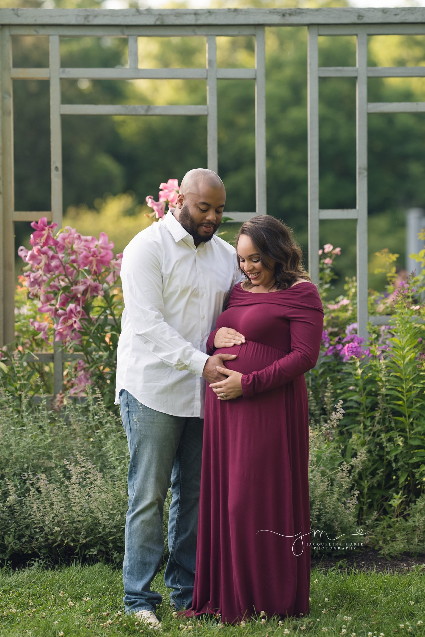 expectant mother wears dress and holds belly with father in columbus ohio for maternity pictures
