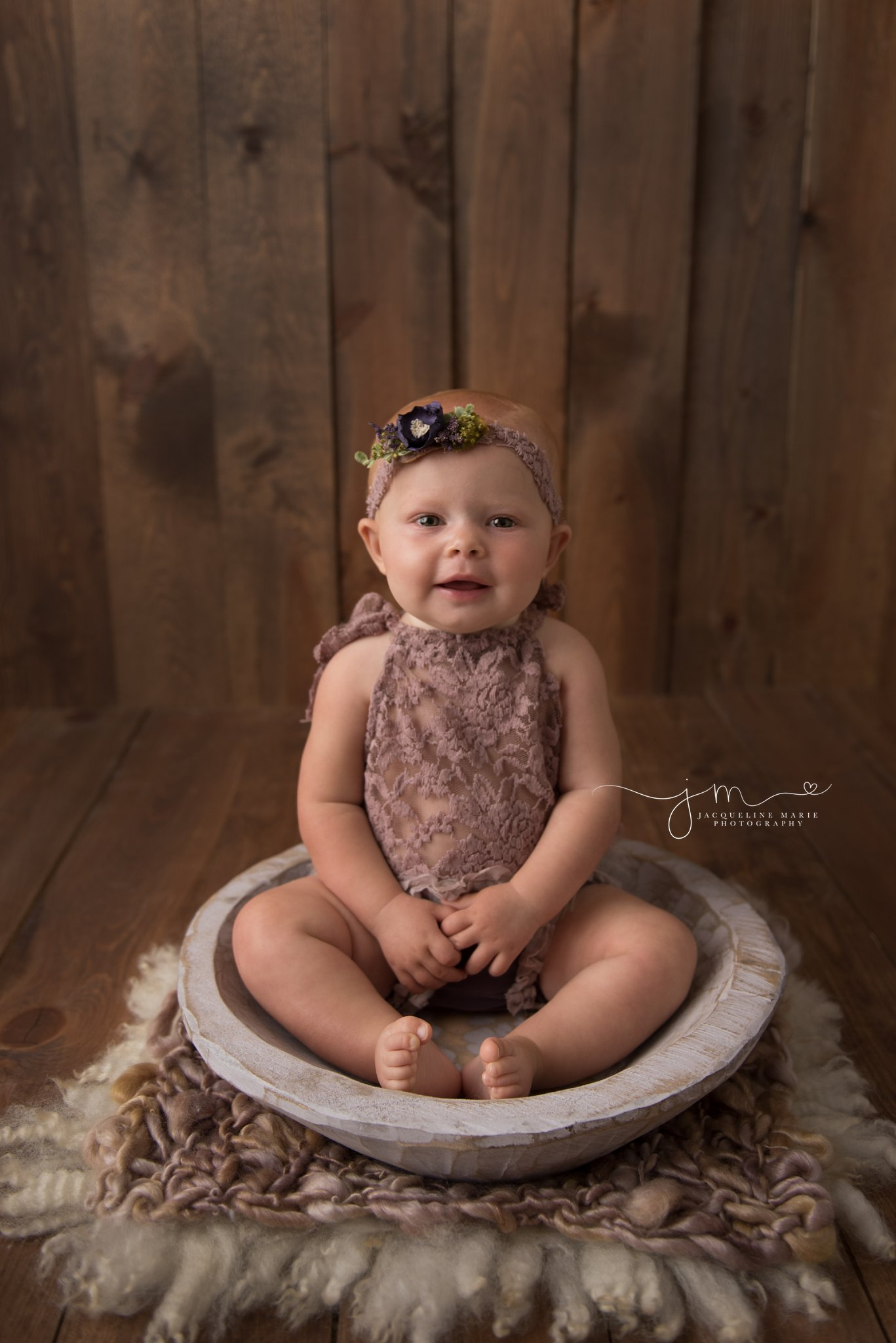 8 month old baby girl sits in wood bowl for child milestone photography in columbus ohio