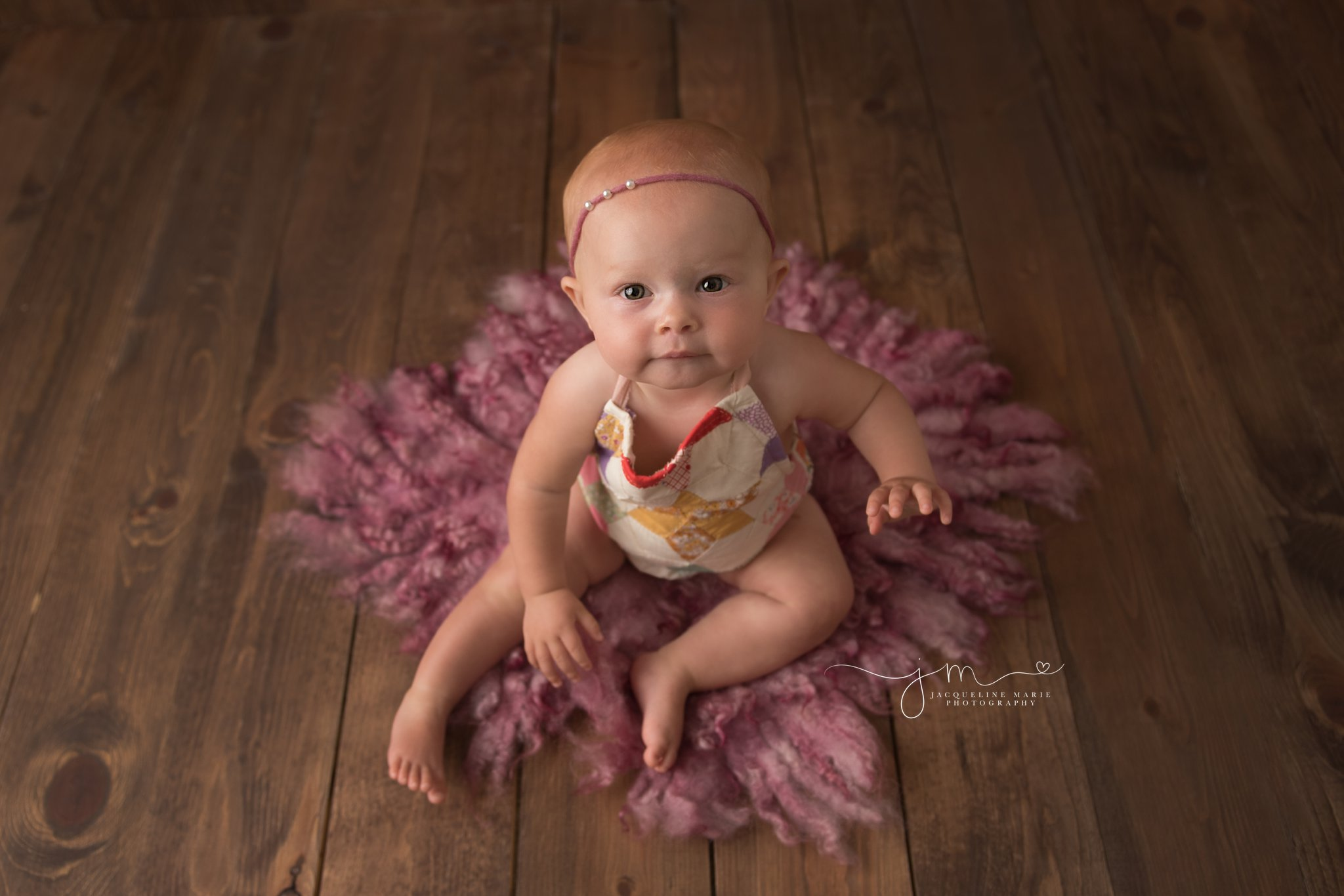 8 month old Scarlett sits on pink felted layer and wood floor for baby milestone pictures in columbus ohio