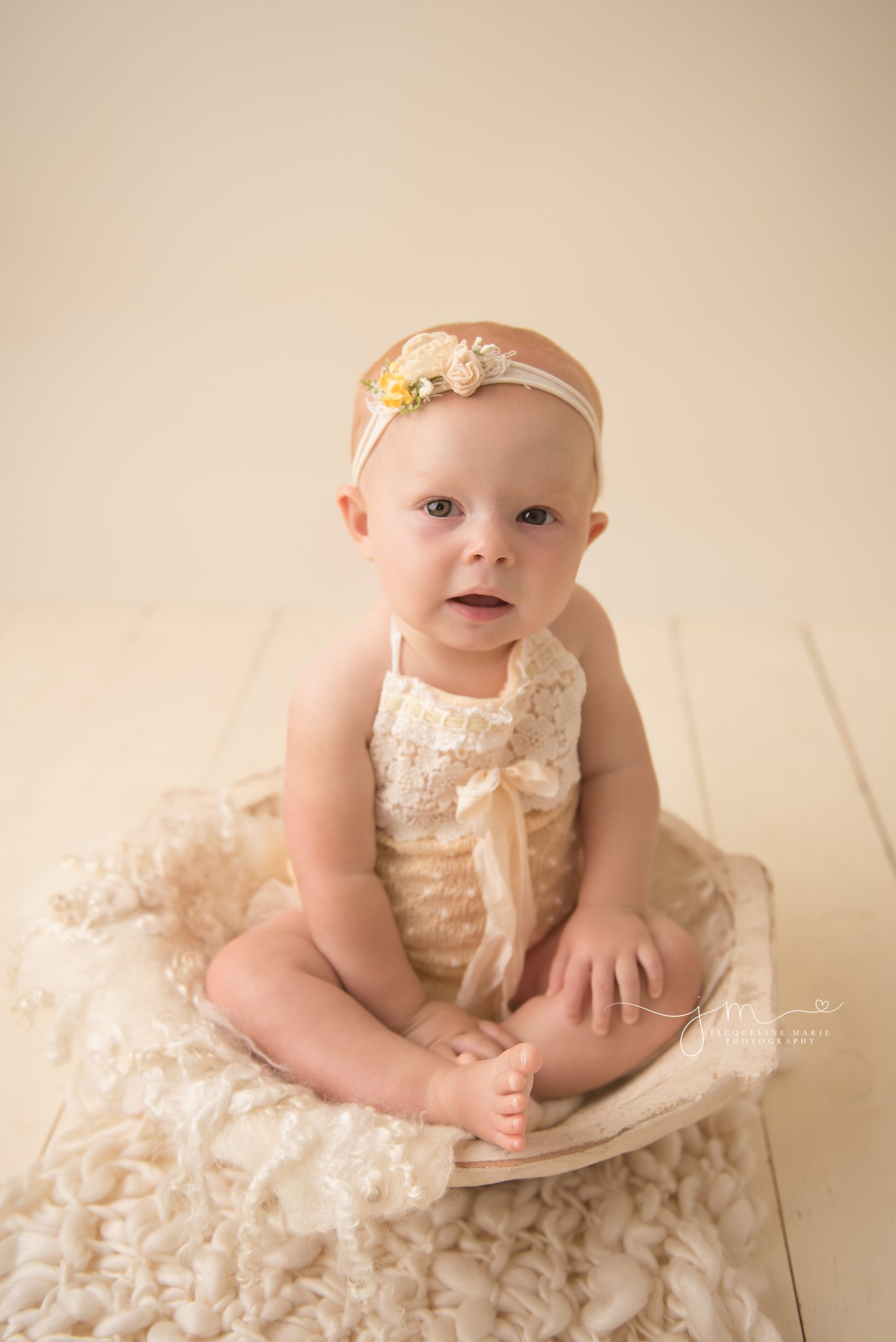 milestone baby girl wears yellow romper and matching headband for children photography pictures in columbus ohio