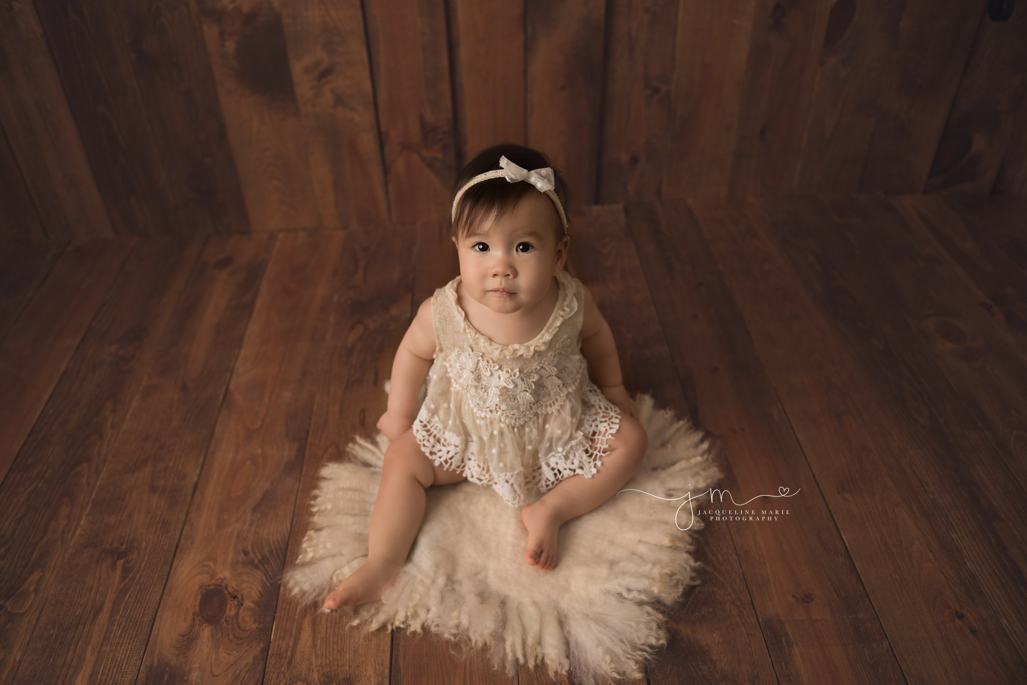 1 year old wears cream lace top and matching headband for first birthday milestone pictures in columbus ohio by jacqueline marie photography