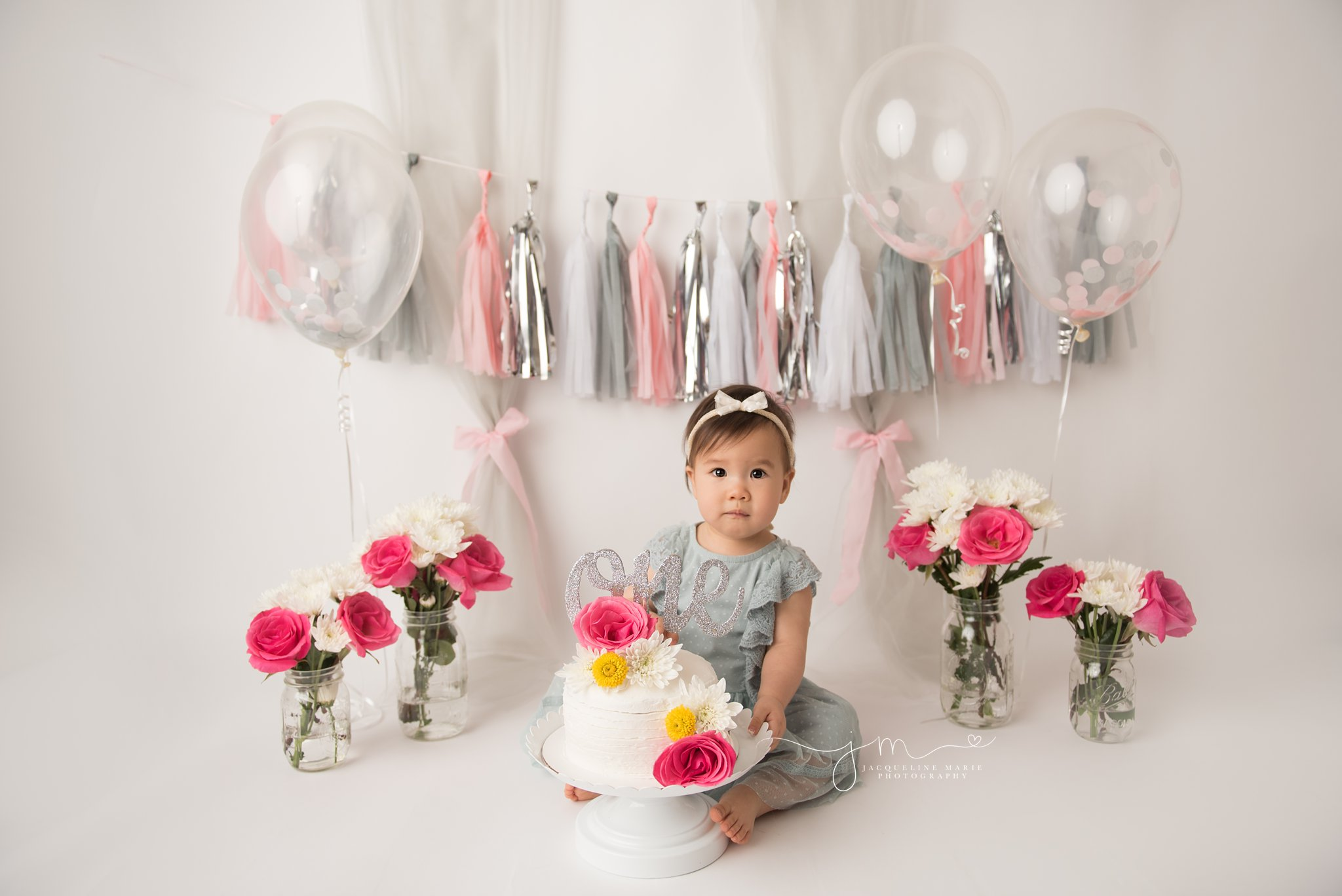first birthday cake smash photographer features baby girl with floral cake in columbus ohio