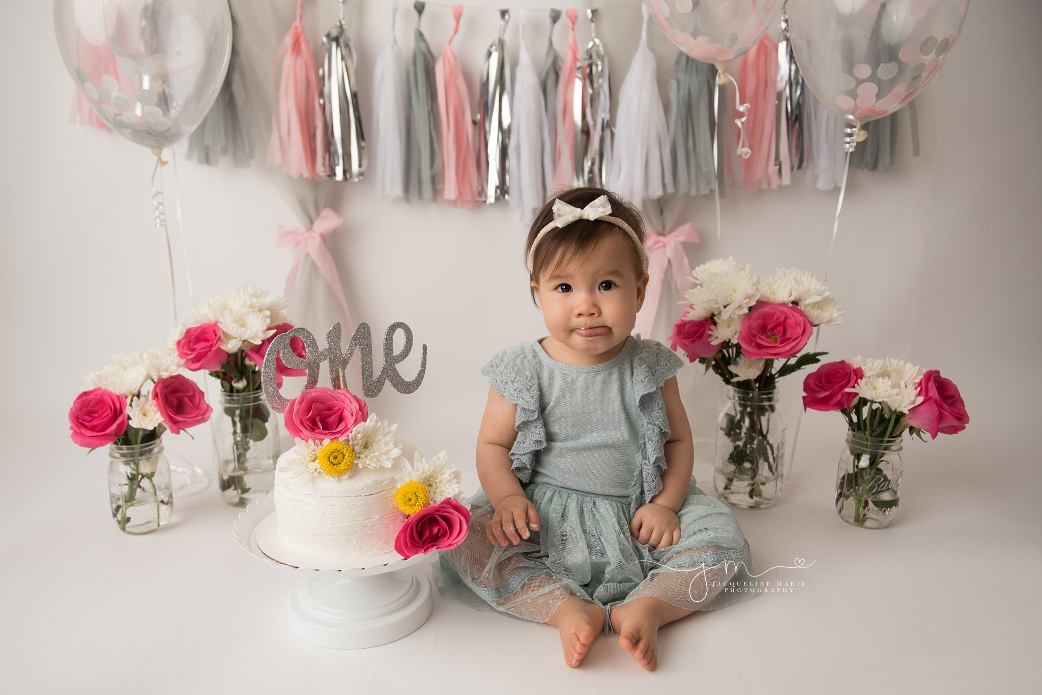 one year old birthday girl sticks her tongue out during her cake smash photo session in columbus ohio