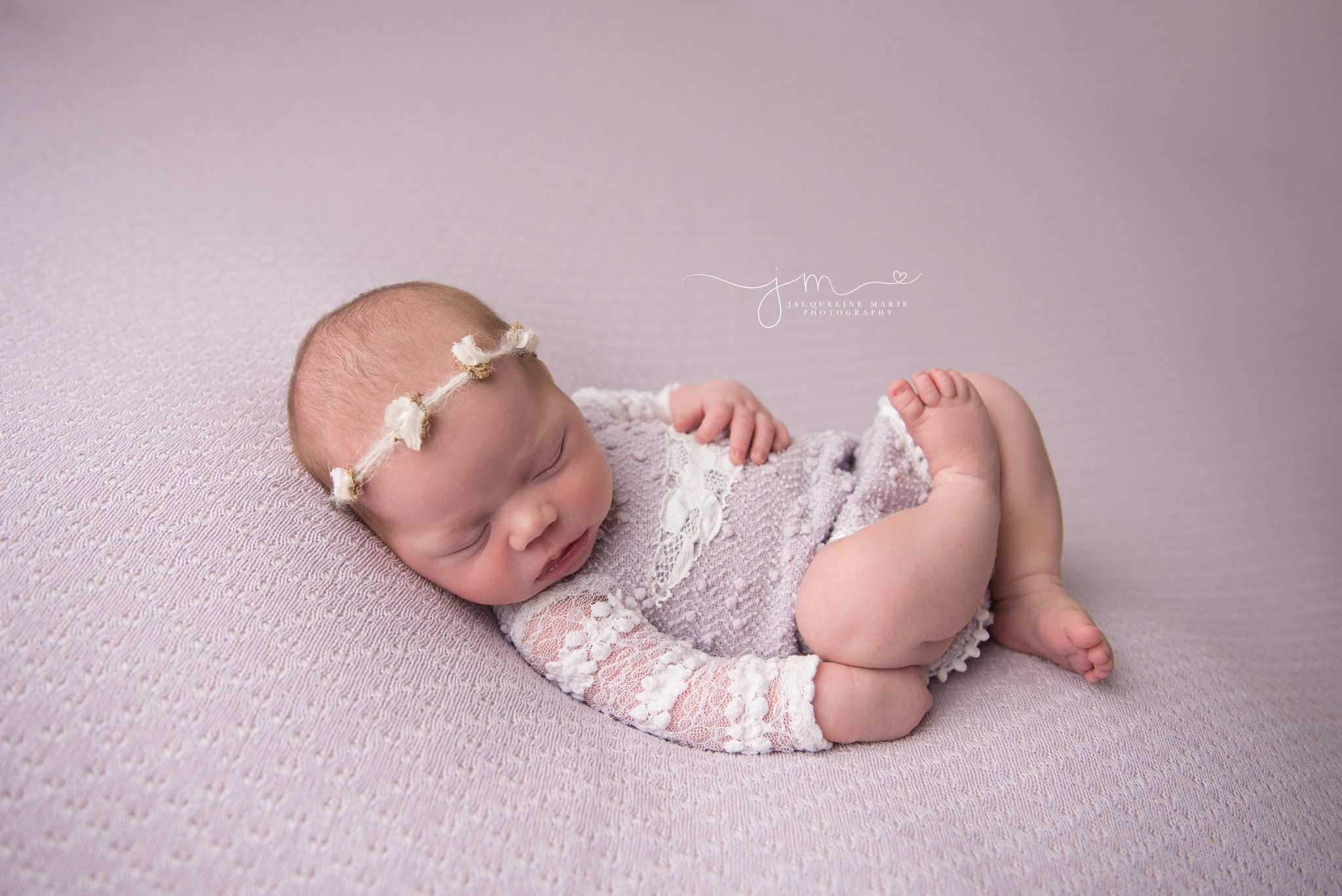 13 day old newborn baby girl wears lavender romper and matching tieback for newborn pictures in columbus ohio