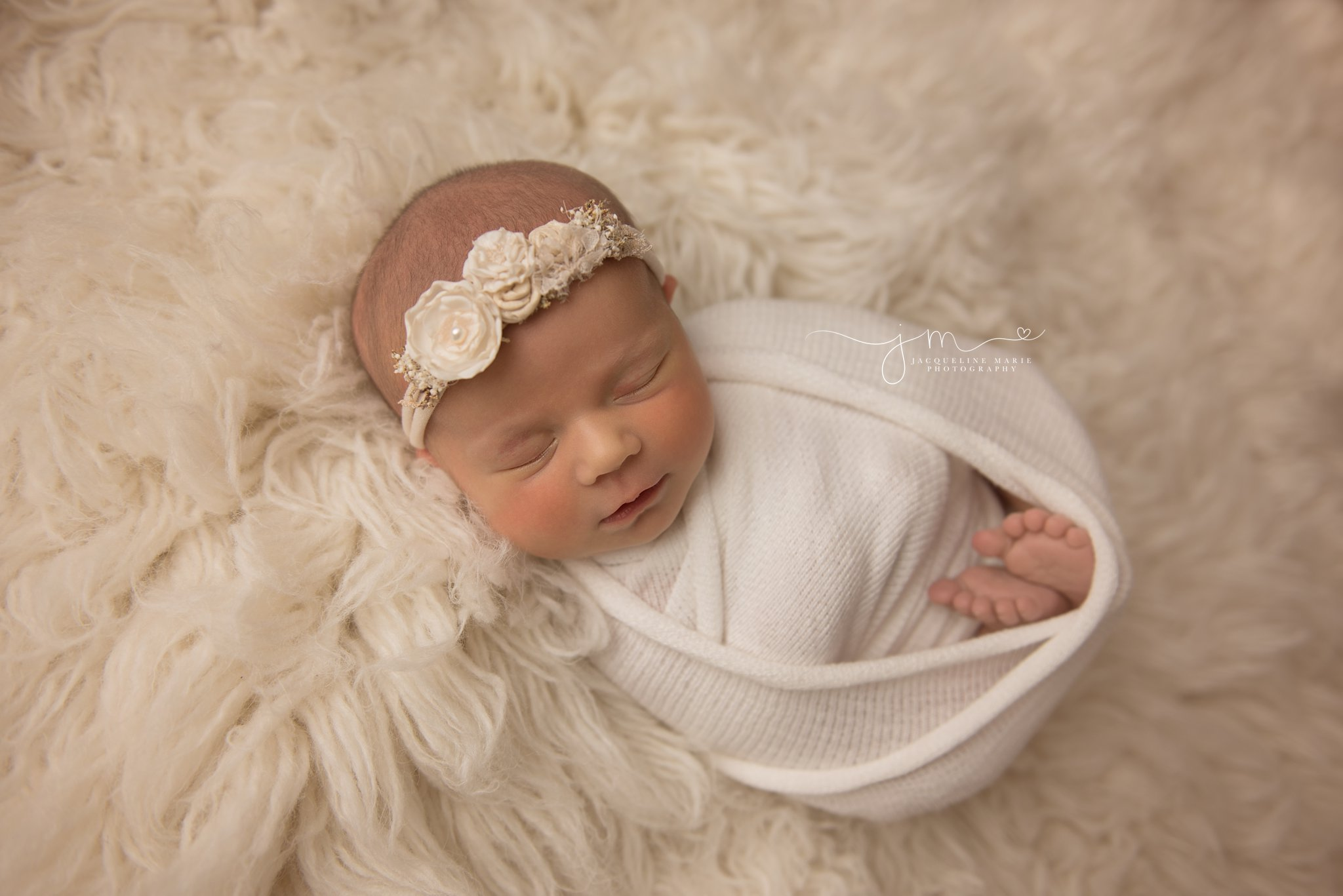 1 week old newborn baby girl swaddled in cream wrap on cream fur rug for newborn photography pictures in columbus ohio