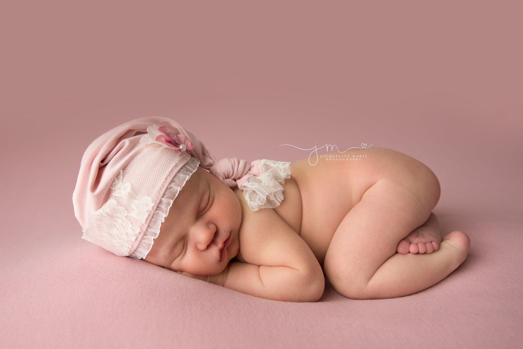 1 week old newborn baby girl wears pink and white lace sleepy hat in columbus ohio for newborn photography session