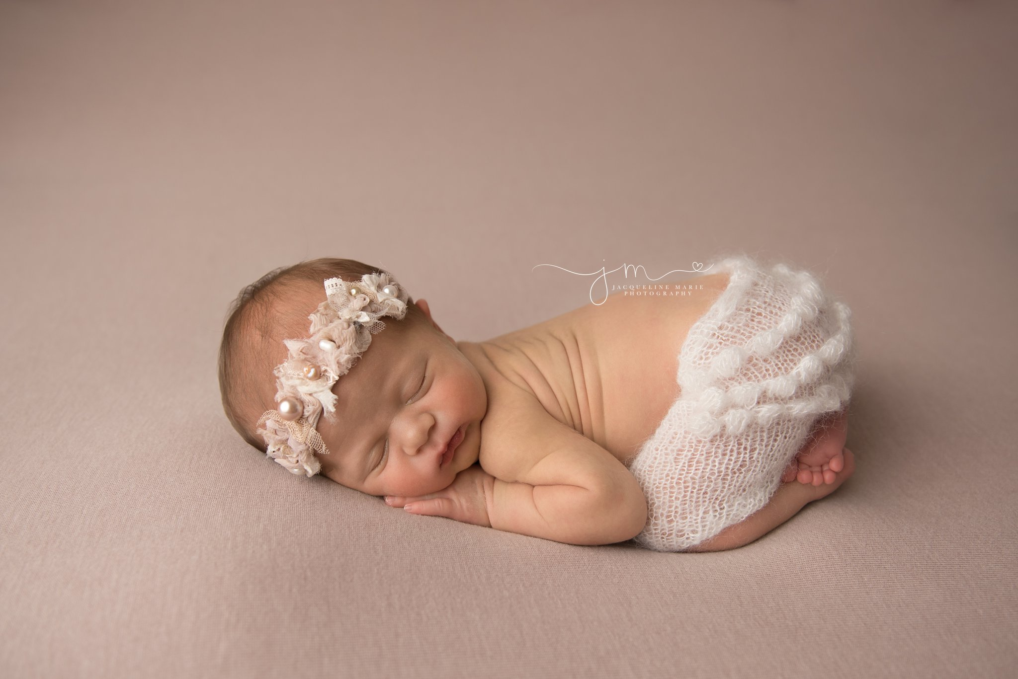 1 week old newborn baby girl wears cream ruffle pants for newborn pictures in columbus ohio
