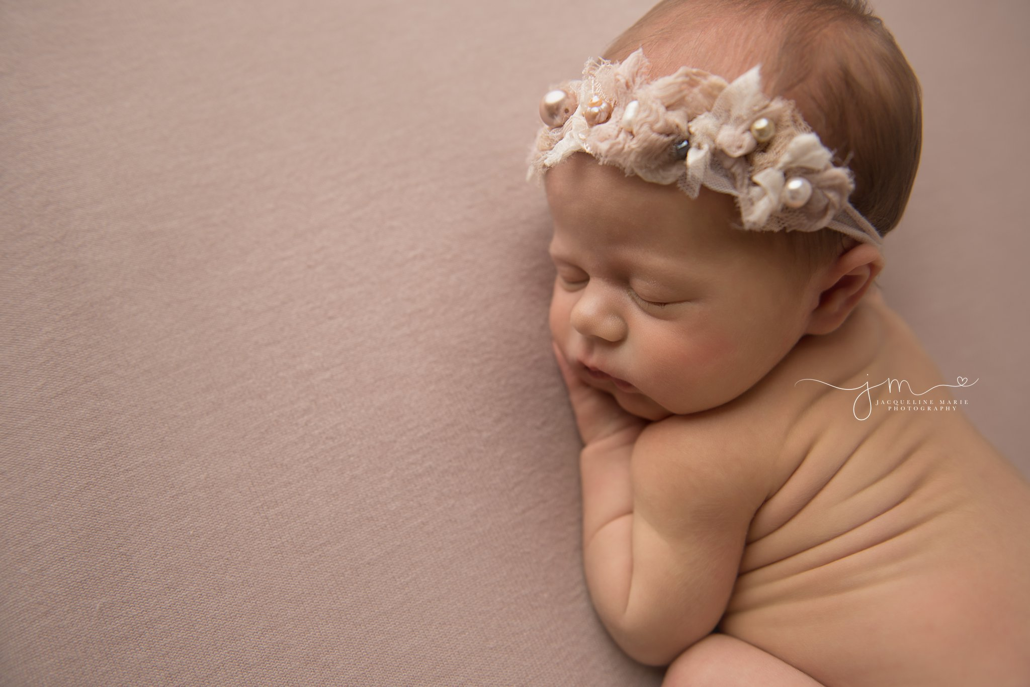 columbus ohio newborn photographer features baby girl sleeping in pink pearl headband for newborn pictures