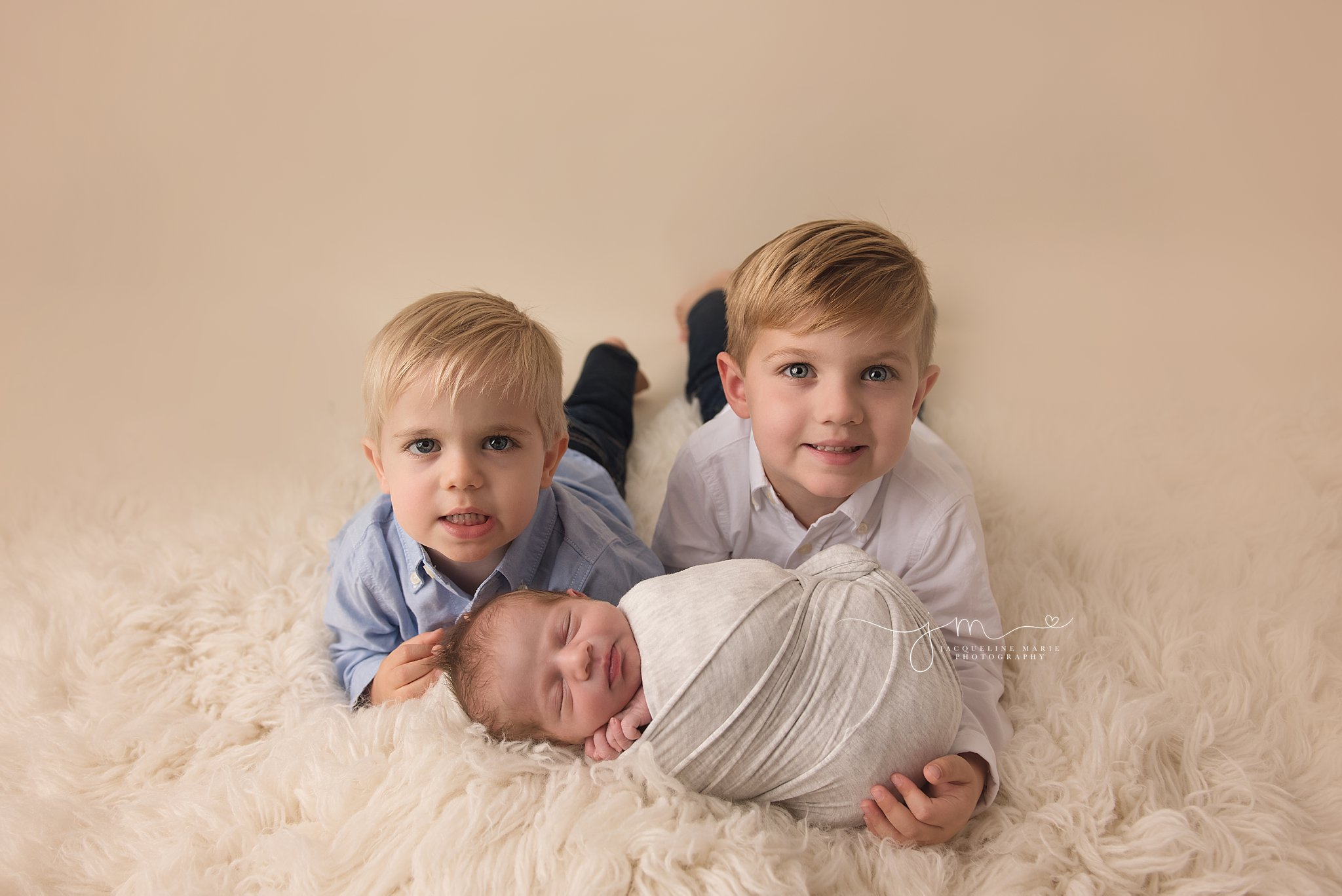 older brothers hug and snuggle newborn baby brother for newborn photography session in columbus ohio