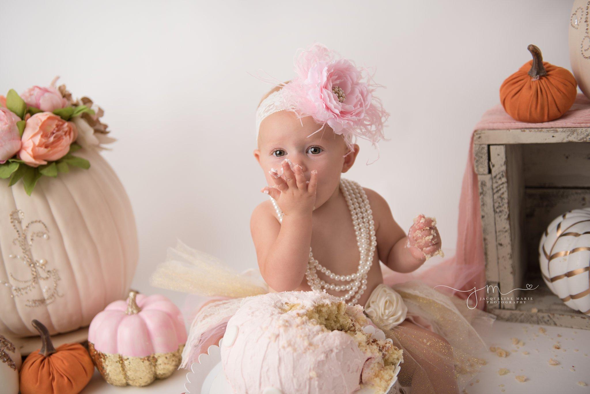 scarlett eats pink pumpkin cake for cake smash birthday pictures in columbus ohio