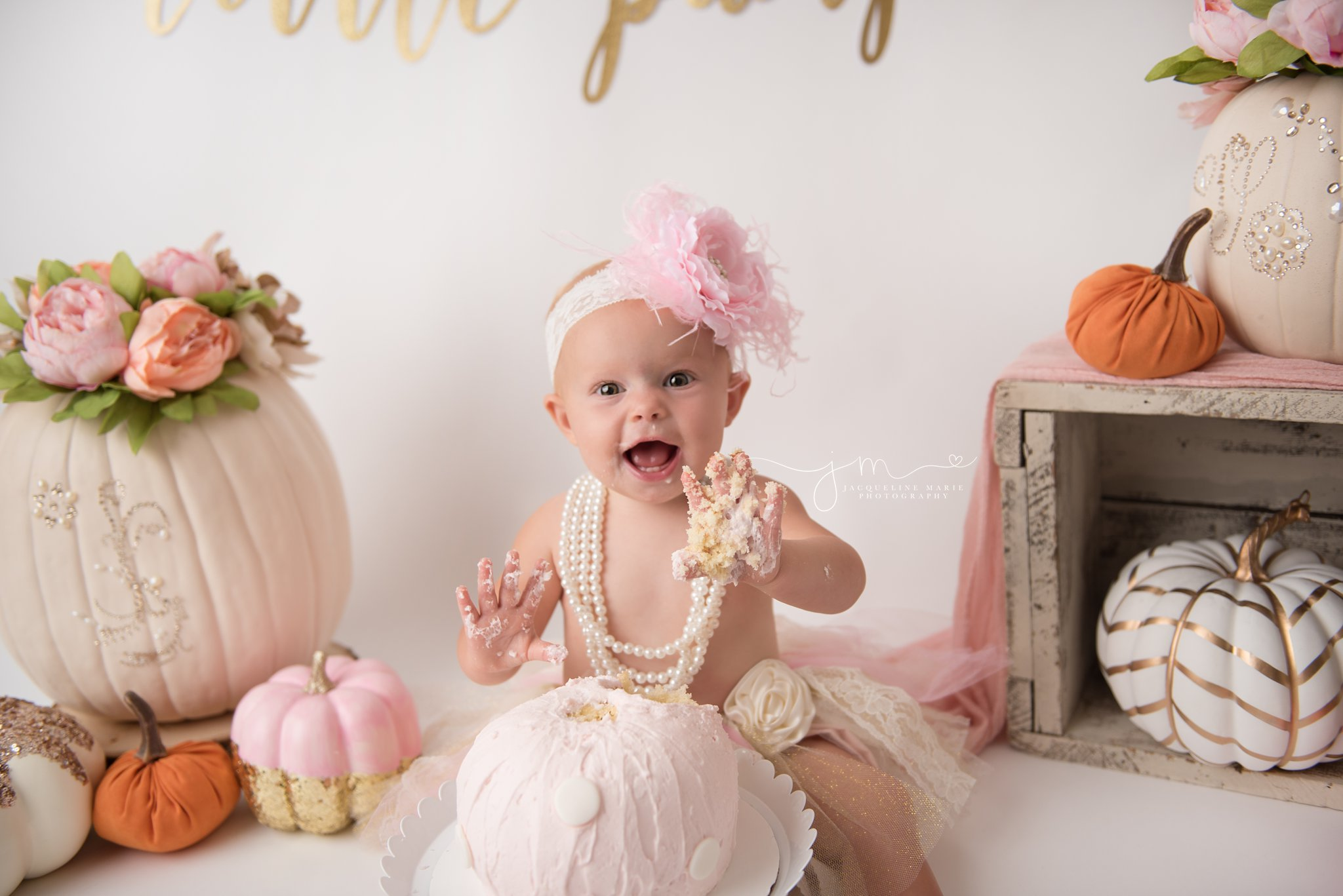 1 year old baby girl smiles with pink cake on her hands for first birthday cake smash photography in Columbus ohio