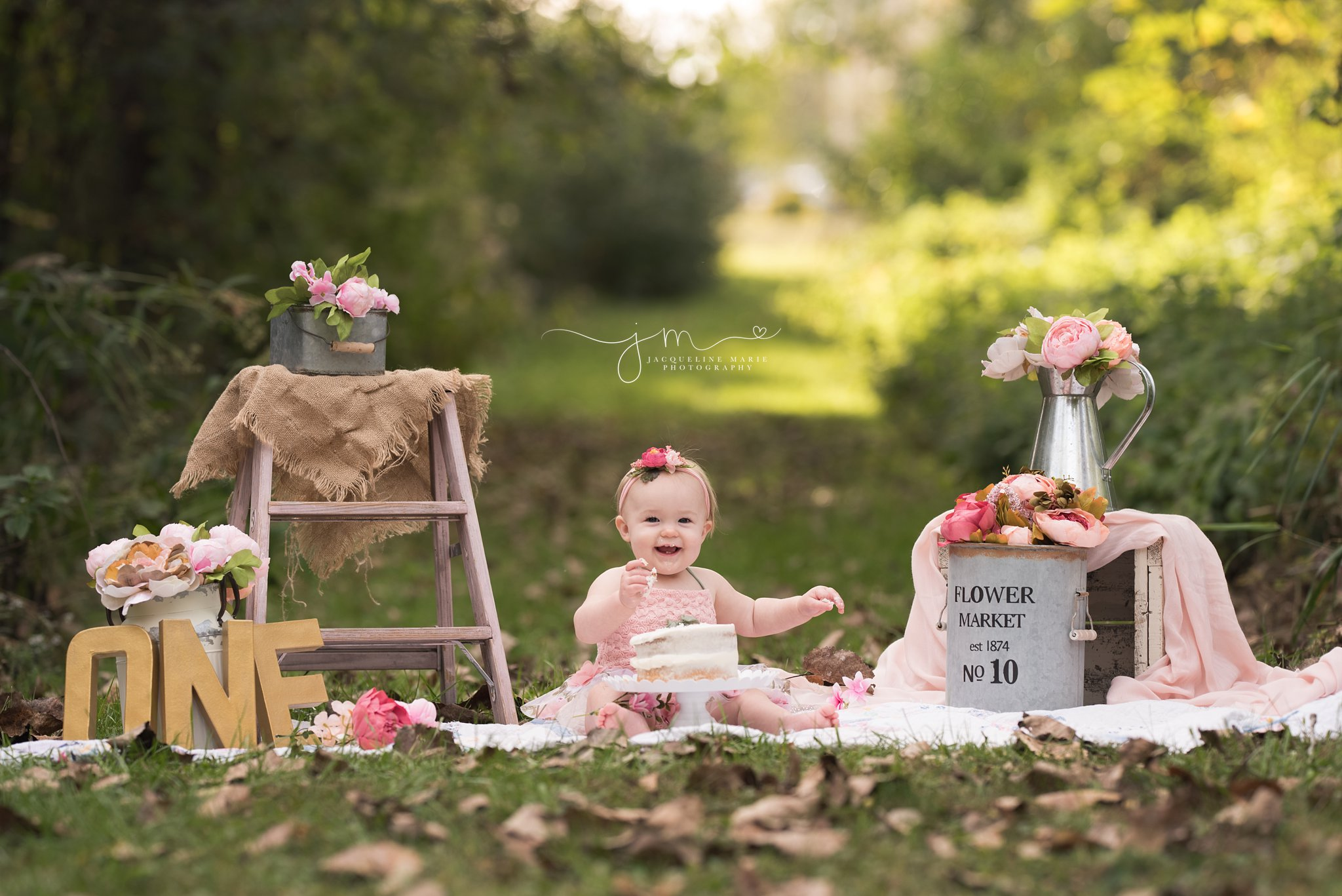 1 year old wears pink floral romper and skirt and smiles while waiting cake of her one year cake smash pictures in columbus ohio