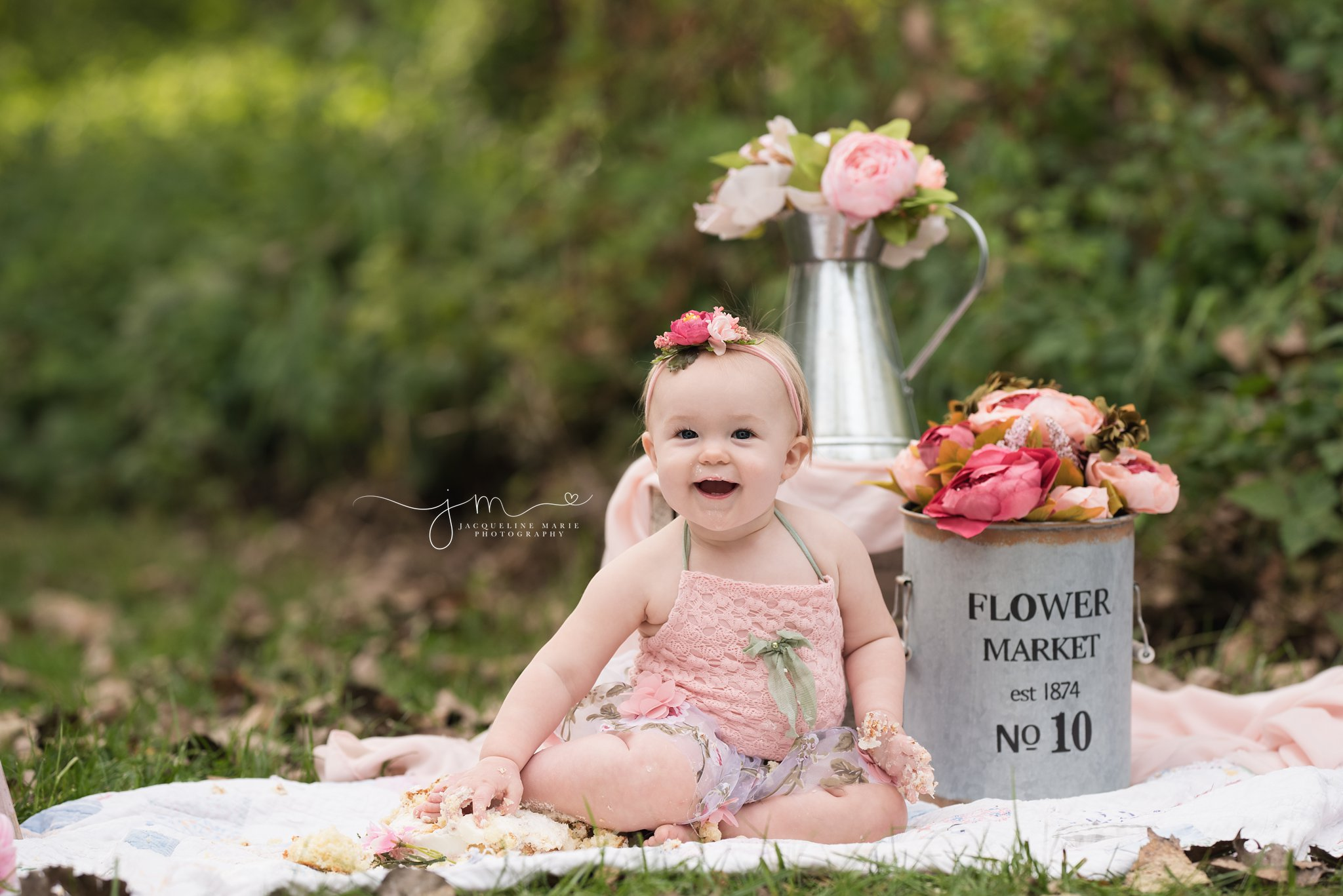 one year old smiles happily while eating cake for her cake smash pictures in columbus ohio