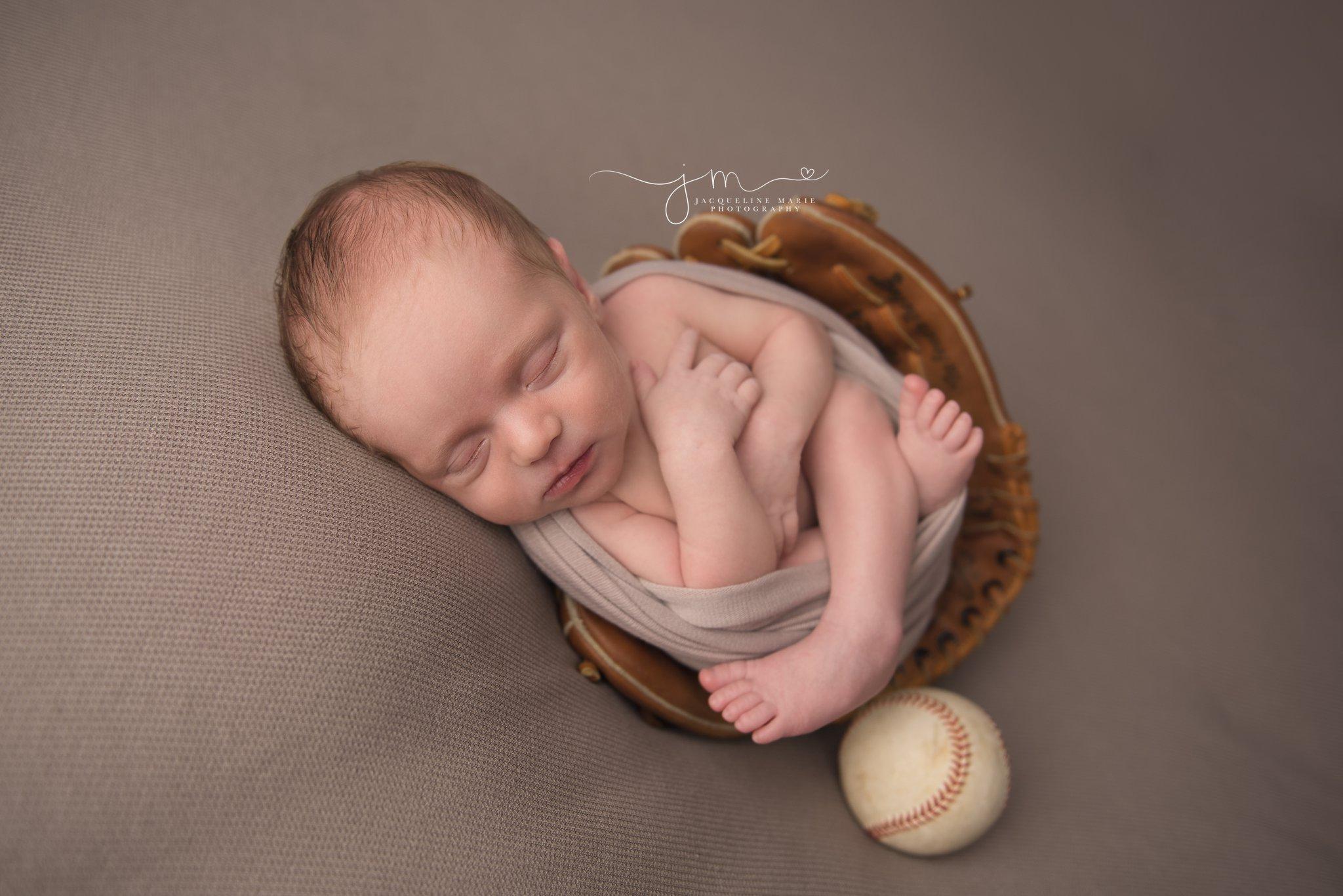 columbus ohio newborn photographer features images of newborn baby boy sleeping is dad's baseball glove