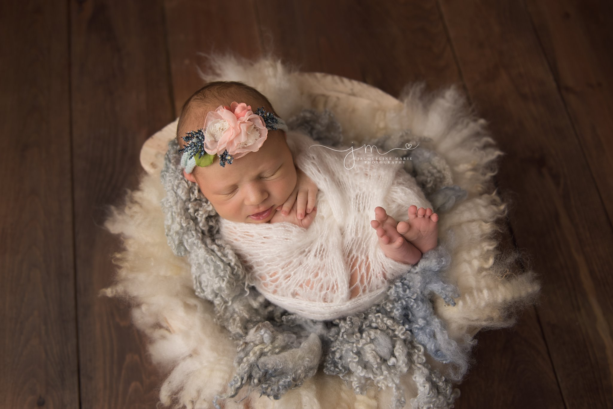 columbus ohio newborn baby girl is swaddled in cream cream while wearing and blue and pink headband for newborn pictures