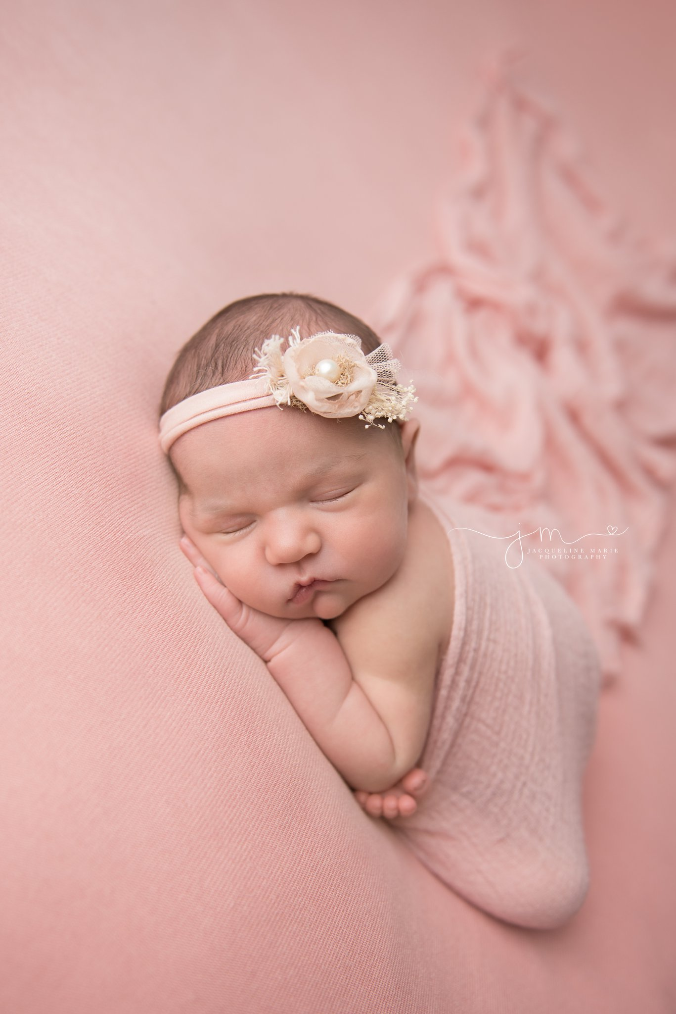 1 week old newborn baby girl is wrapped in a pink wrap and matching headband for newborn photography session in columbus ohio