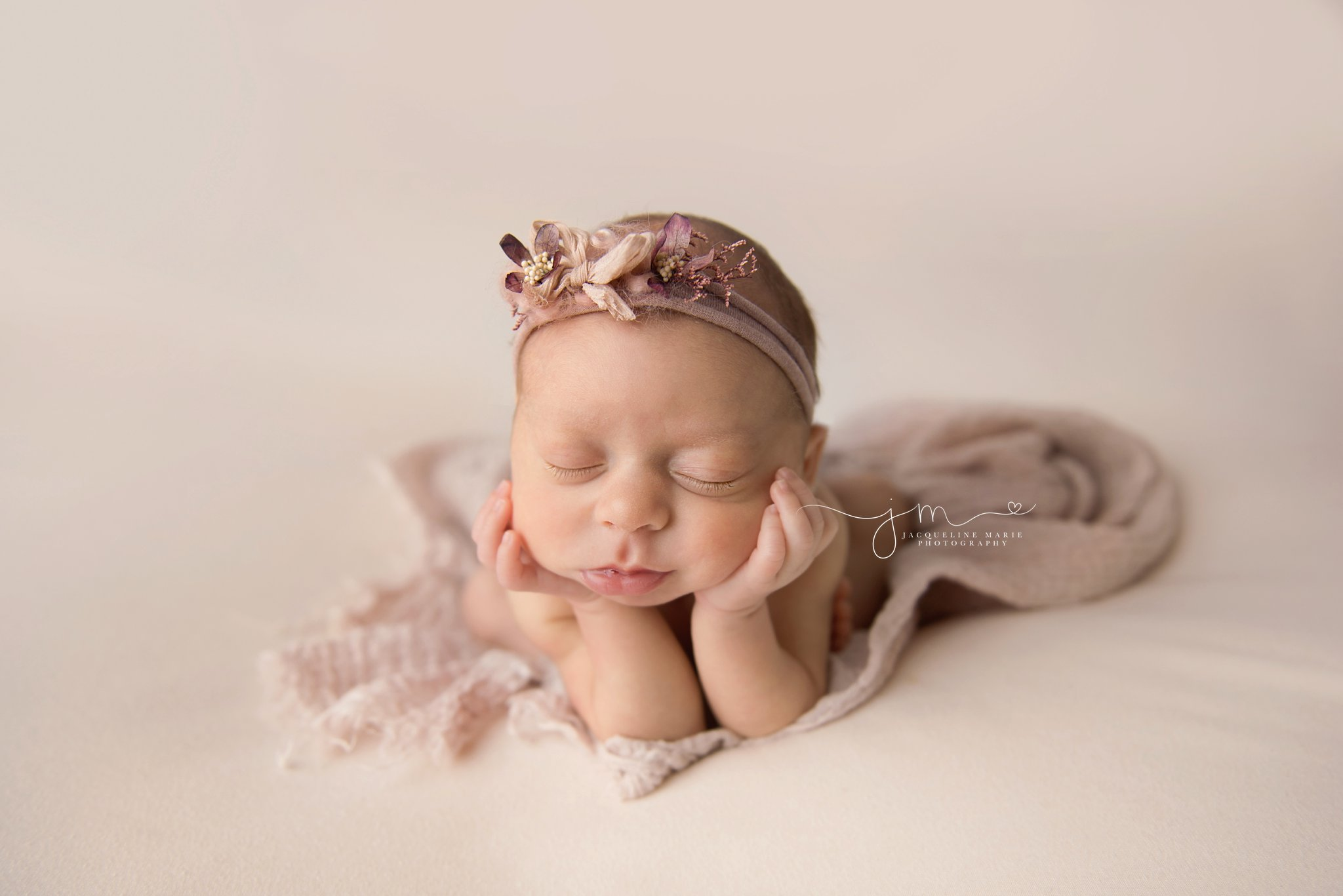 columbus ohio newborn baby girl wears pink and purple headband while posed with her chin in her hands for newborn photography session