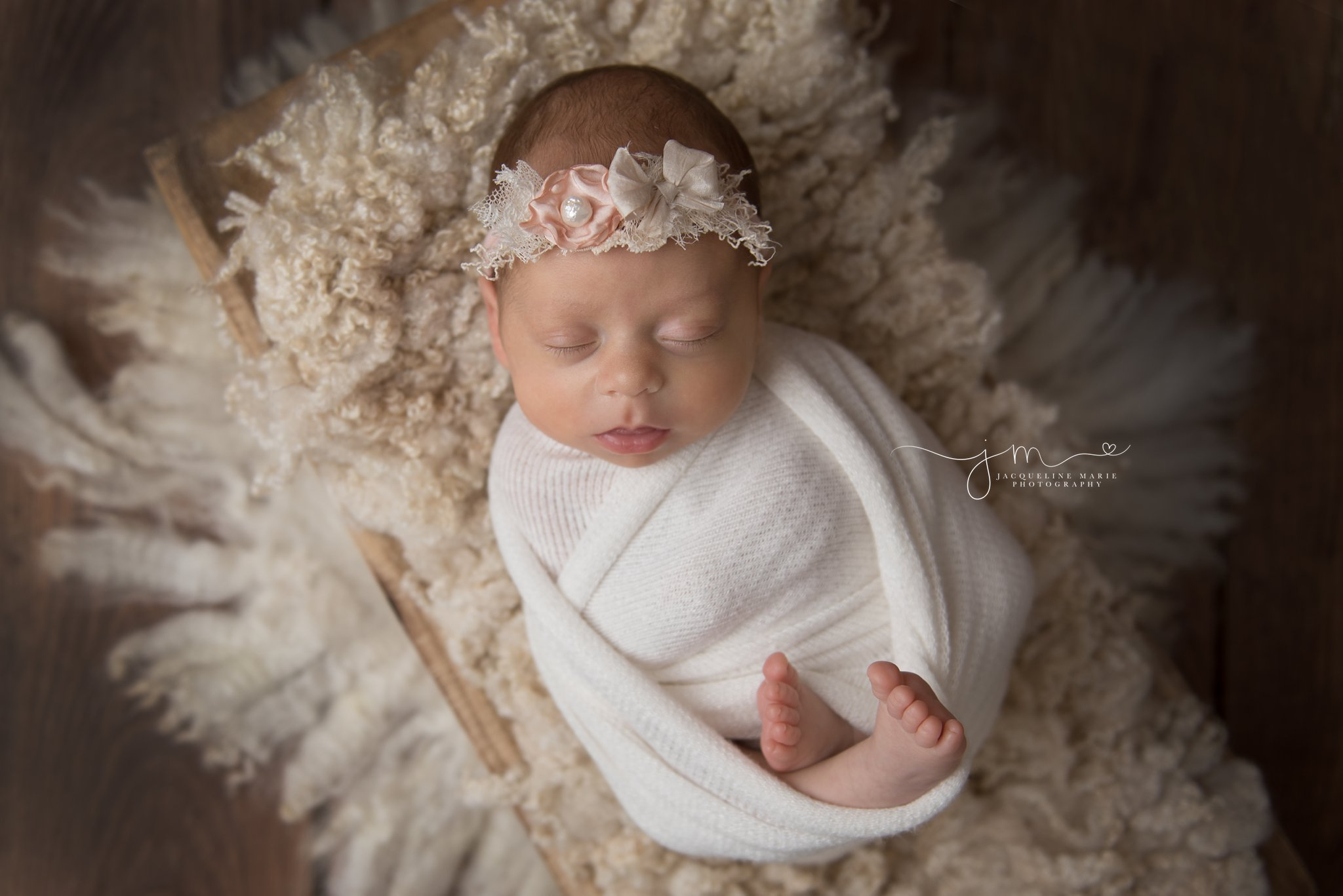6 week old newborn baby girl wears pink and cream headband while swaddled at jacqueline marie photography studio in columbus ohio