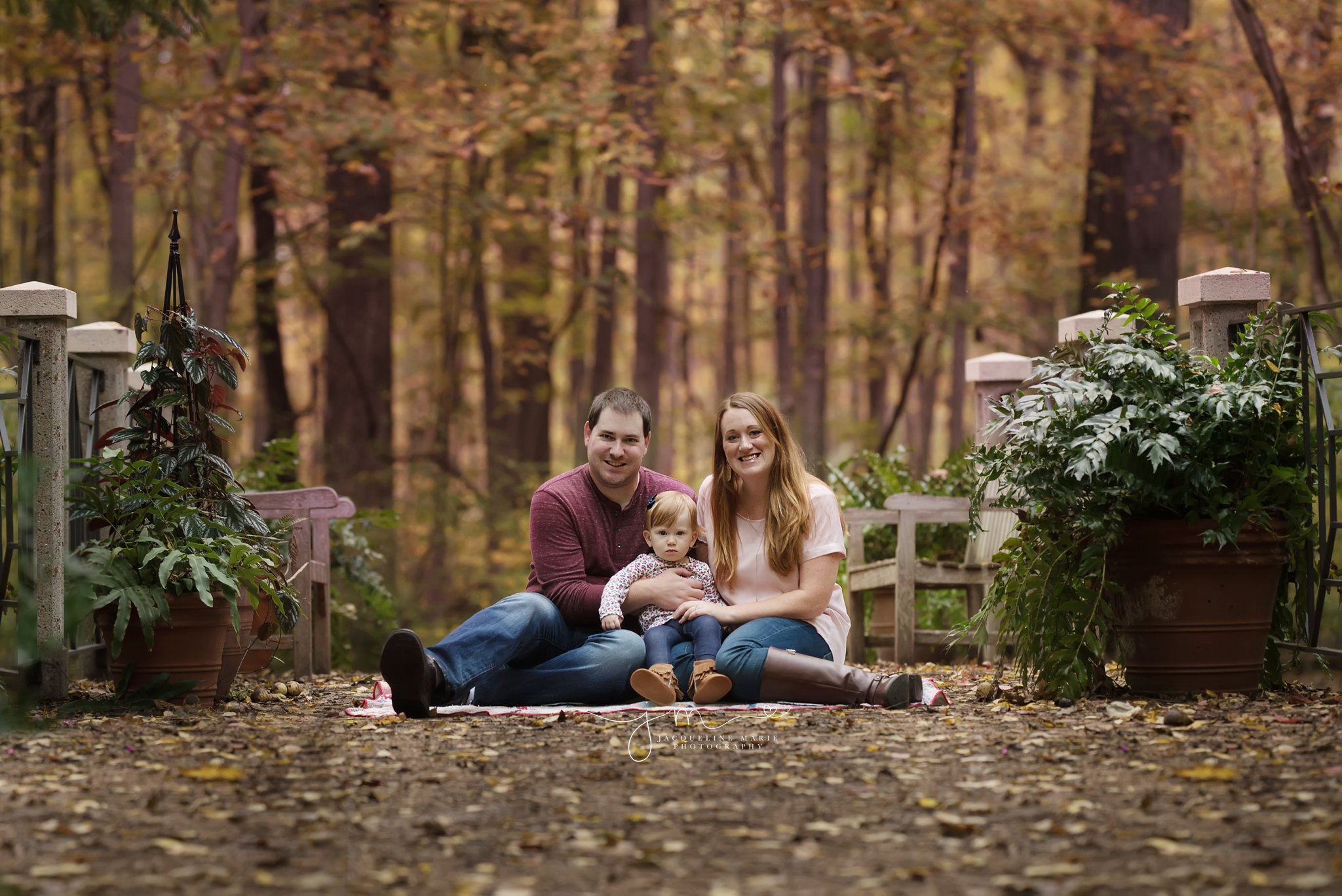 columbus ohio family photographer features family on beautiful fall foliage sitting on bridge  for family portraits
