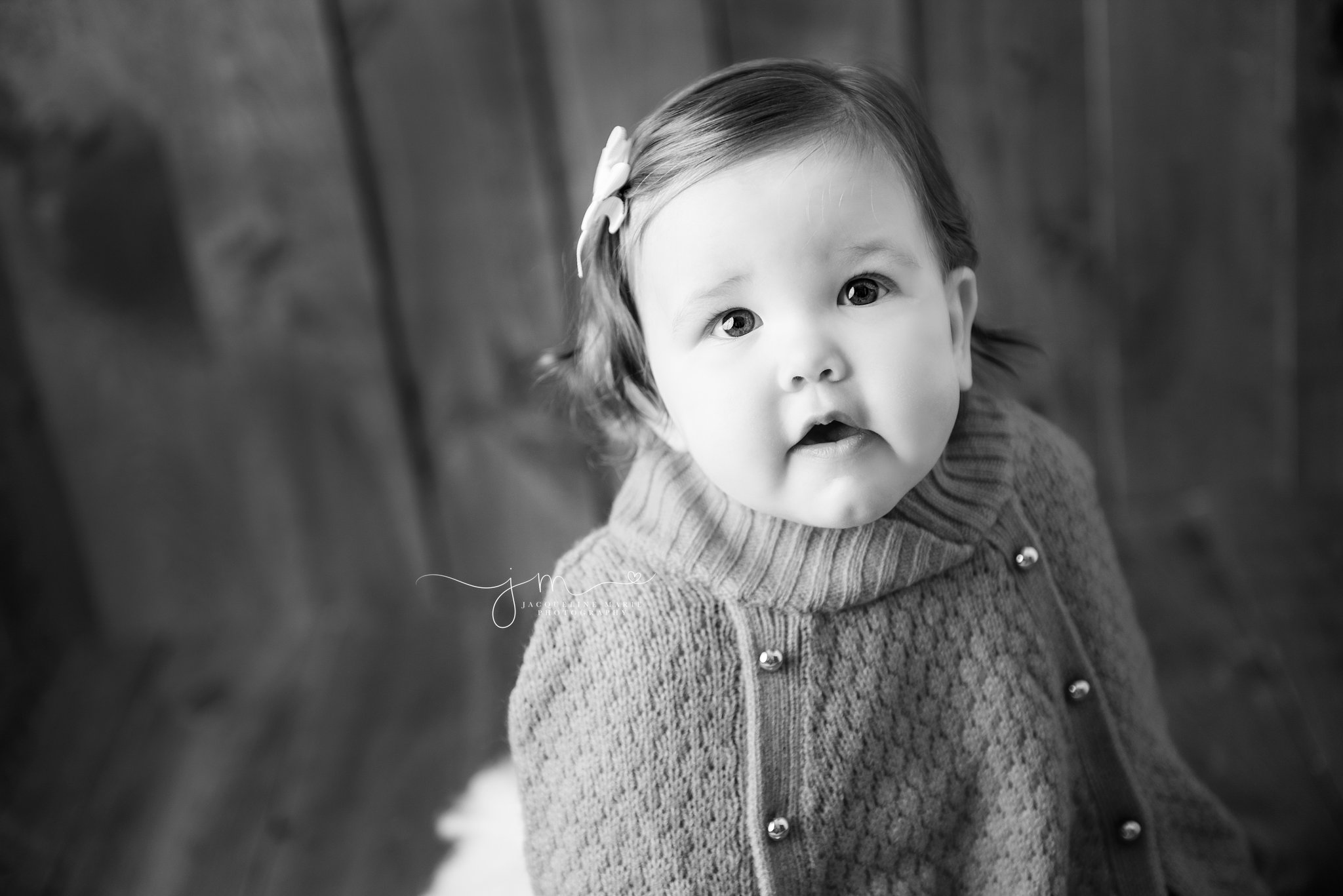 1 year old margot smiles while sitting on wood bucket in columbus ohio for first birthday portraits