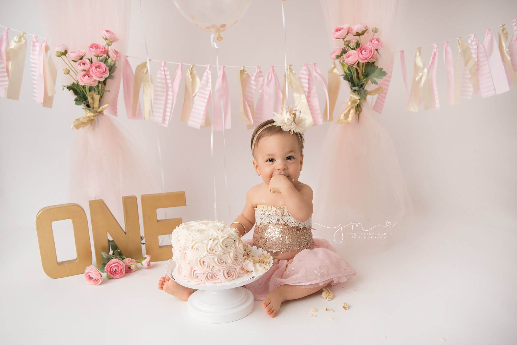 baby girl in columbus ohio eats cake during first birthday cake smash photography session