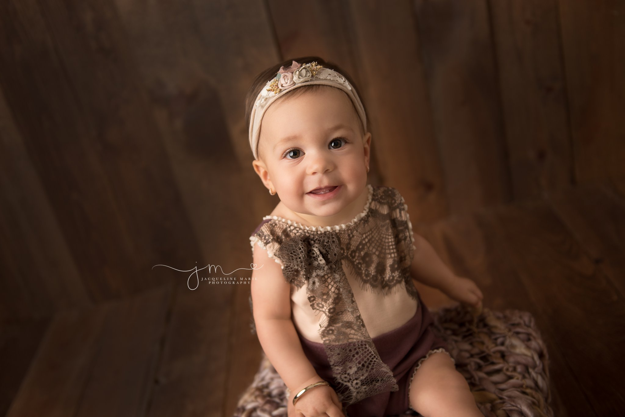 columbus ohio children photographer styles session with 1 year old girl wearing cream and plum romper and matching headband for first birthday portraits