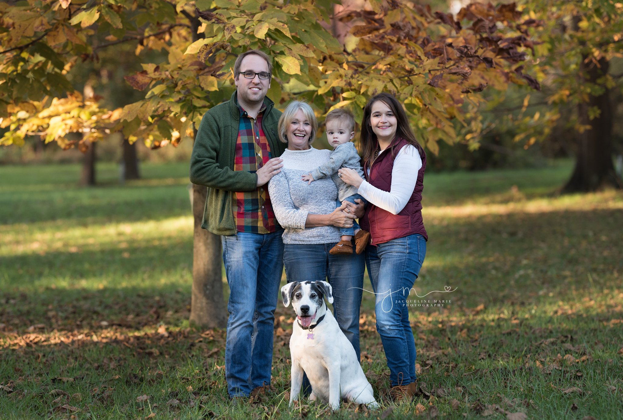 mother, father, son and grandmother stand near fall tree with family dog for outdoor family photography in columbus ohio