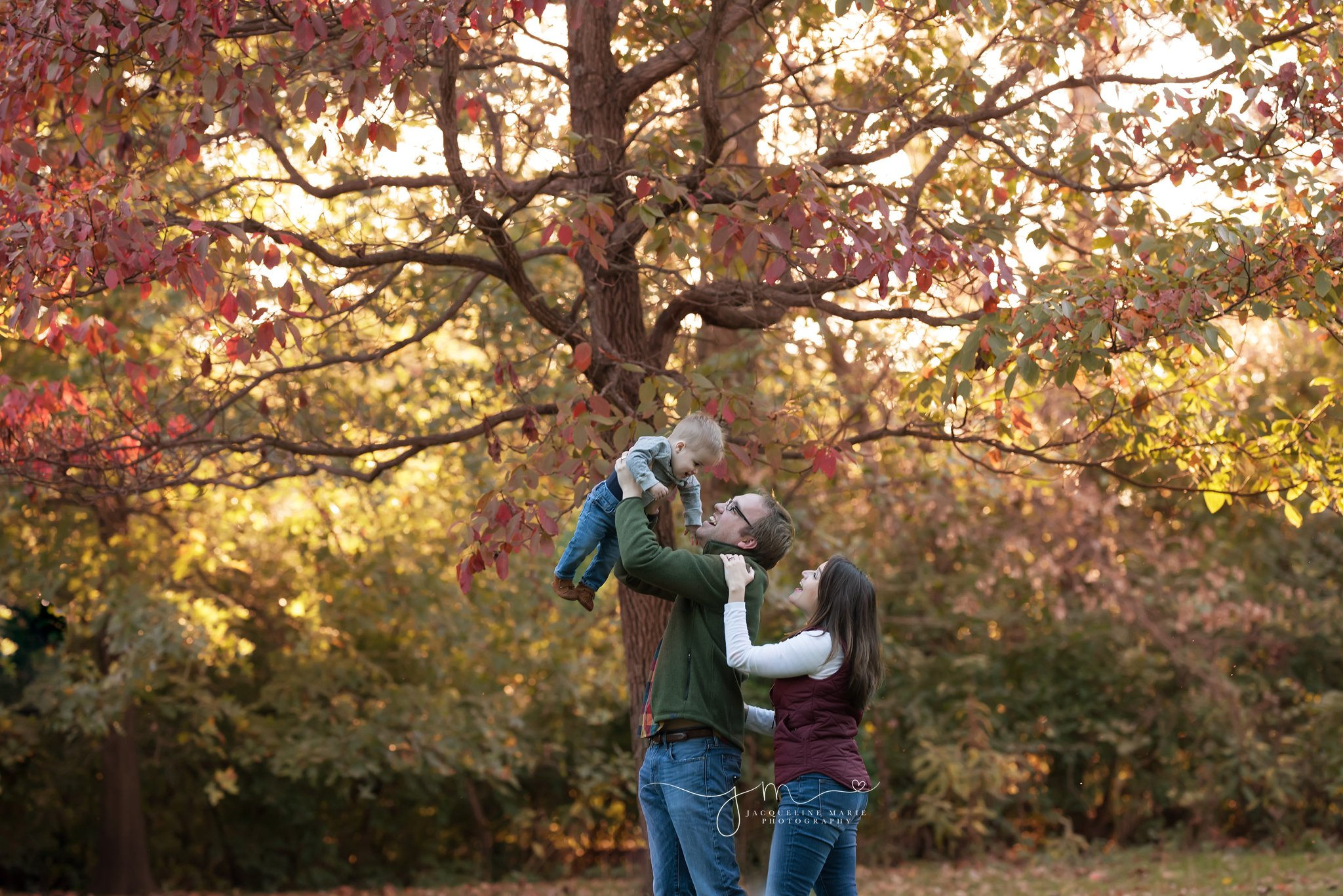 father holds son in the air while smiling for fall family portraits in columbus ohio