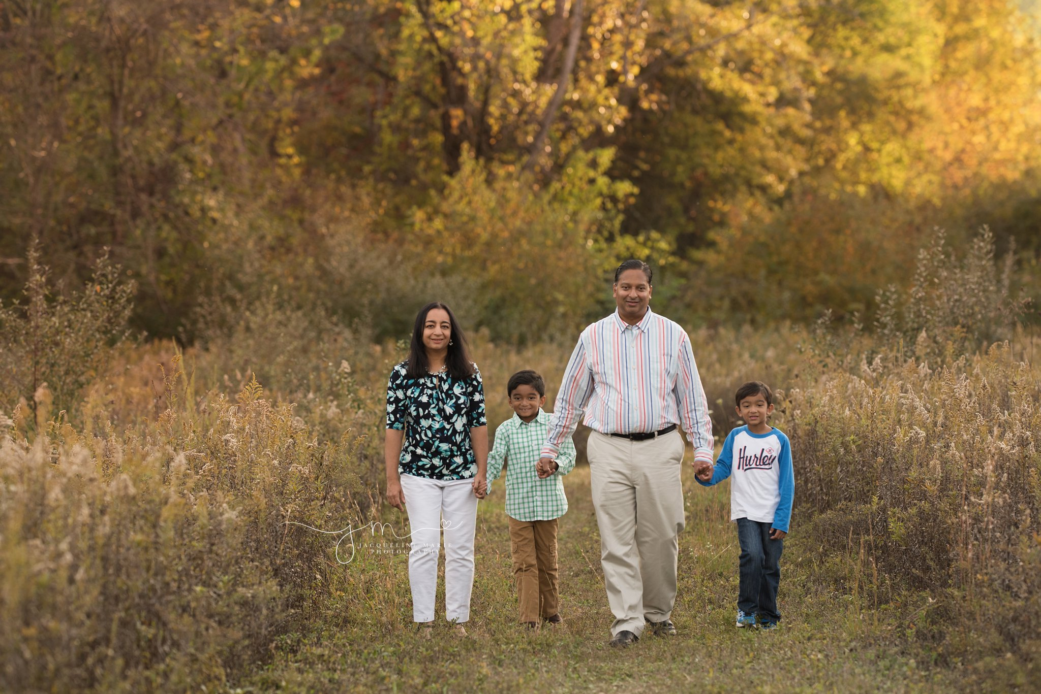 family of four walk together holding hands during family photograph session in columbus ohio