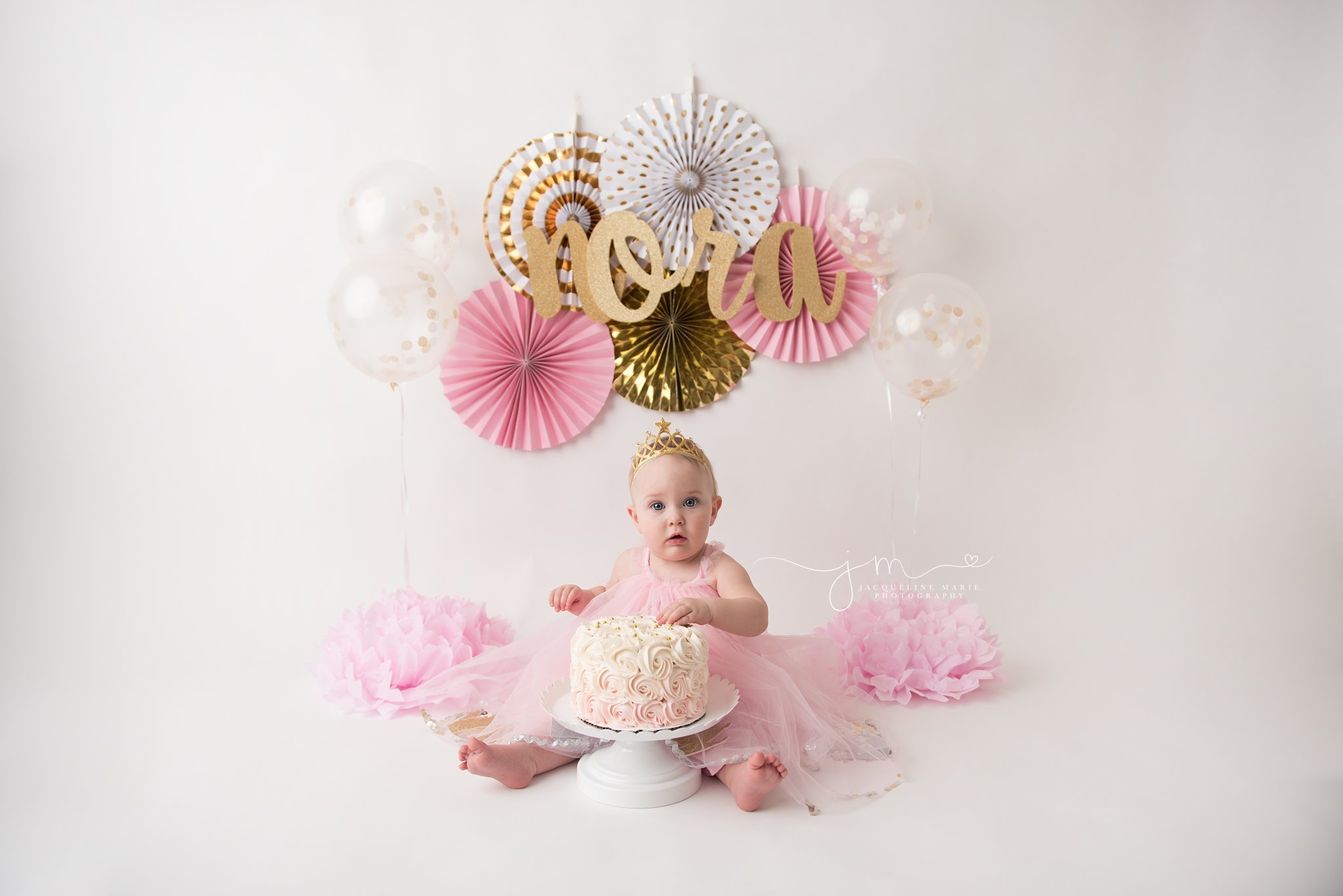 columbus ohio cake smash photographer features pink and gold setup with balloons