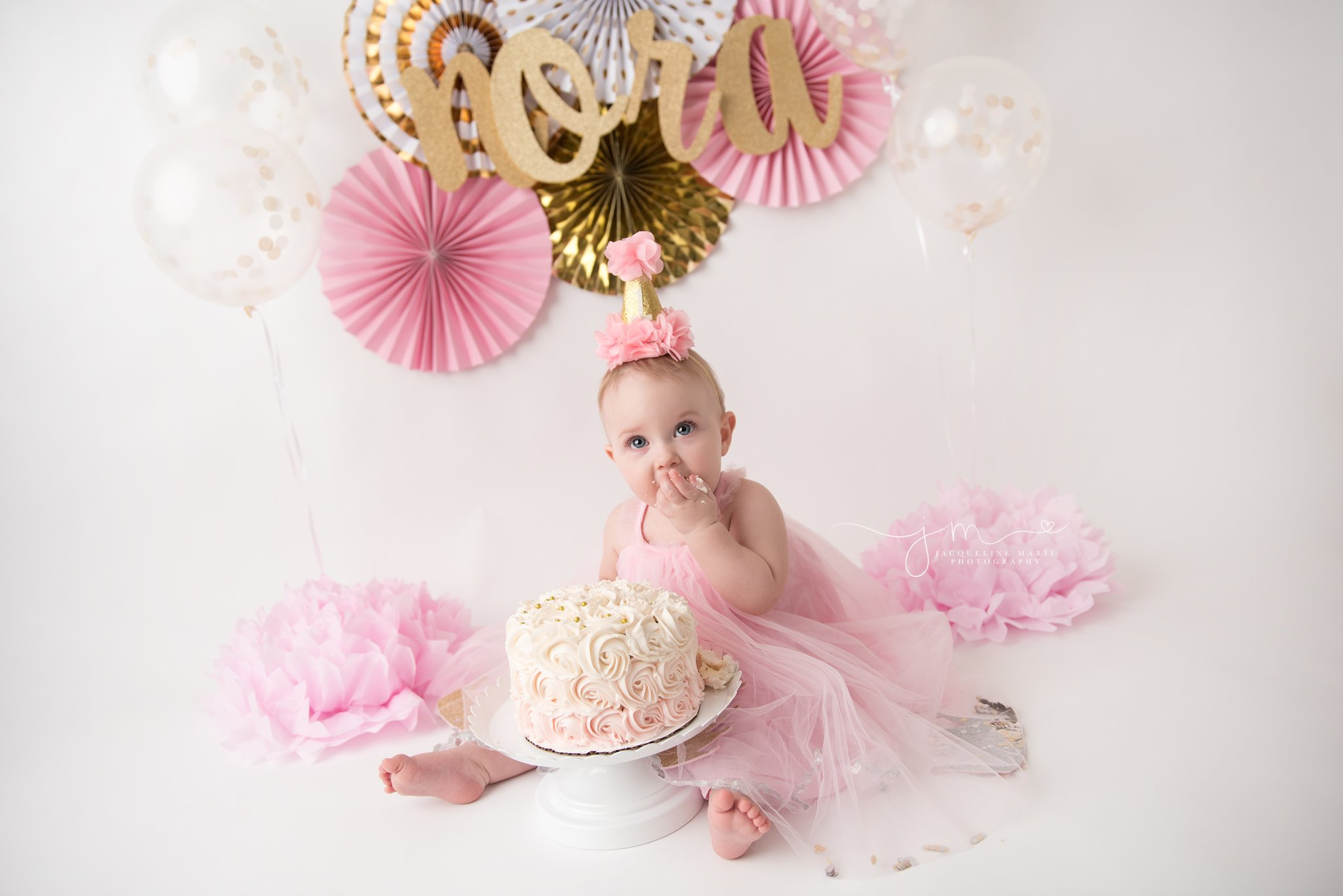 1 year old girl eats pink and cream cake for her cake smash session in columbus ohio