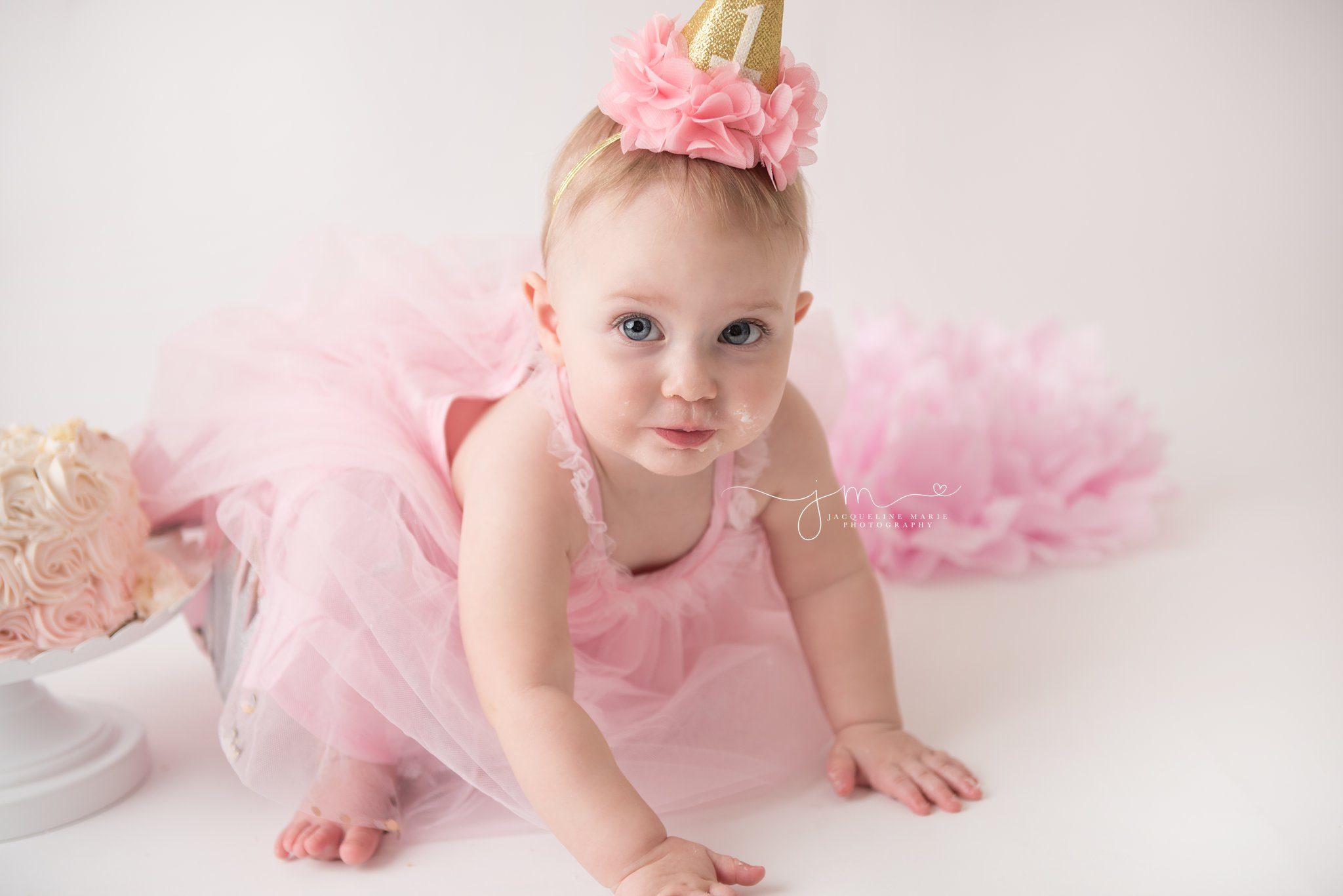 first birthday photographer features baby girl wearing pink dress and gold hat for cake smash pictures in columbus ohio