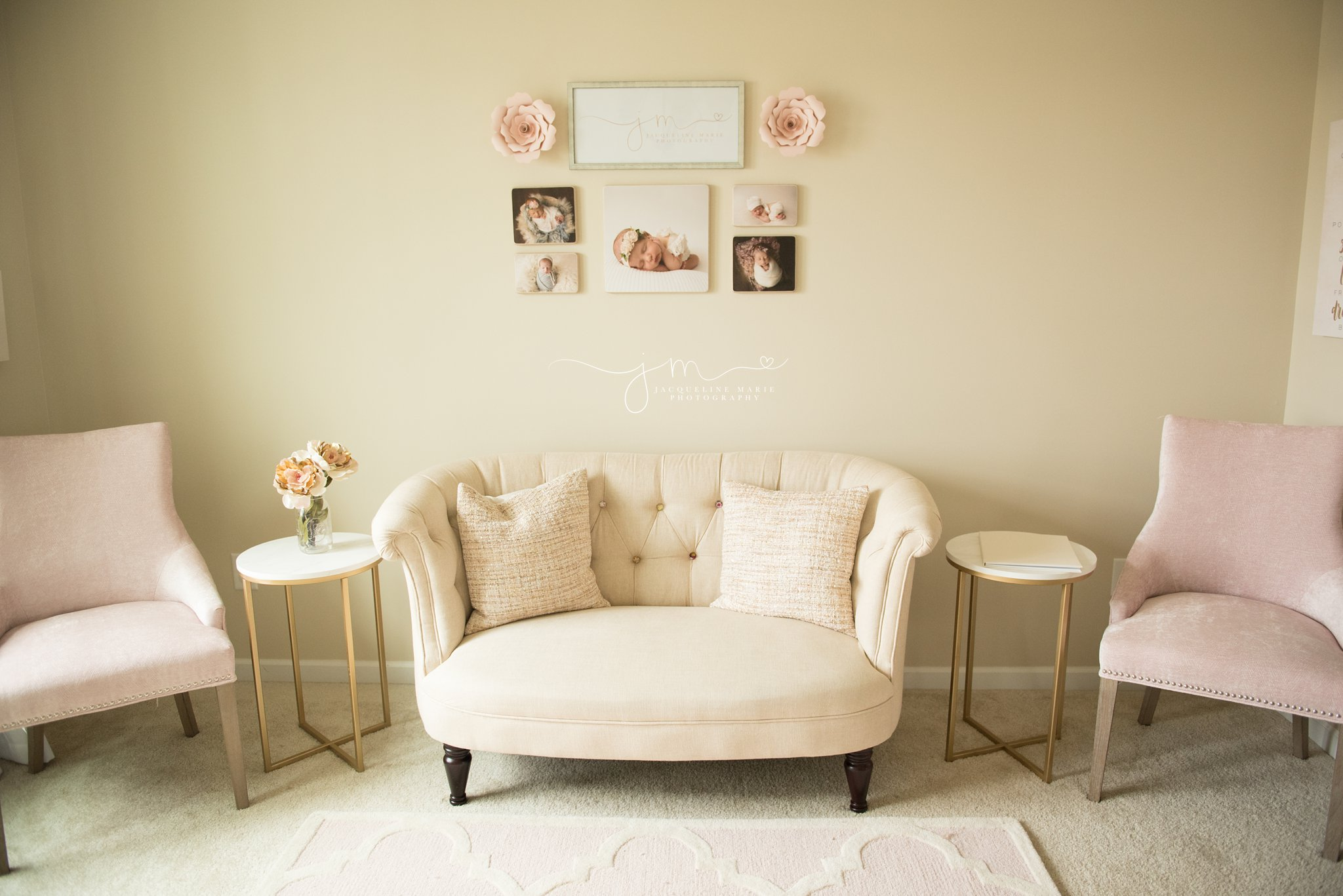 newborn photography studio inspiration features a cream couch and pink chairs to welcome families