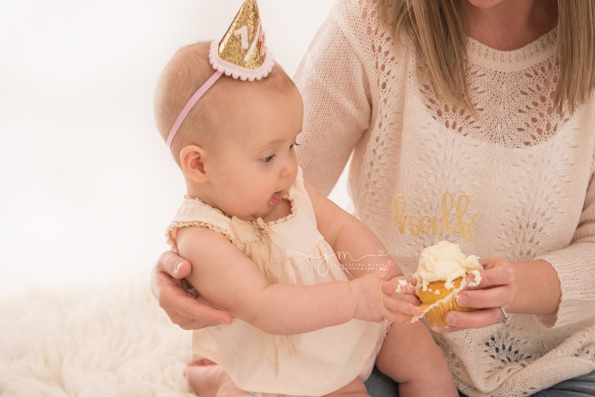 columbus ohio baby girl wears a half birthday hat and holds a cupcake for milestone baby pictures