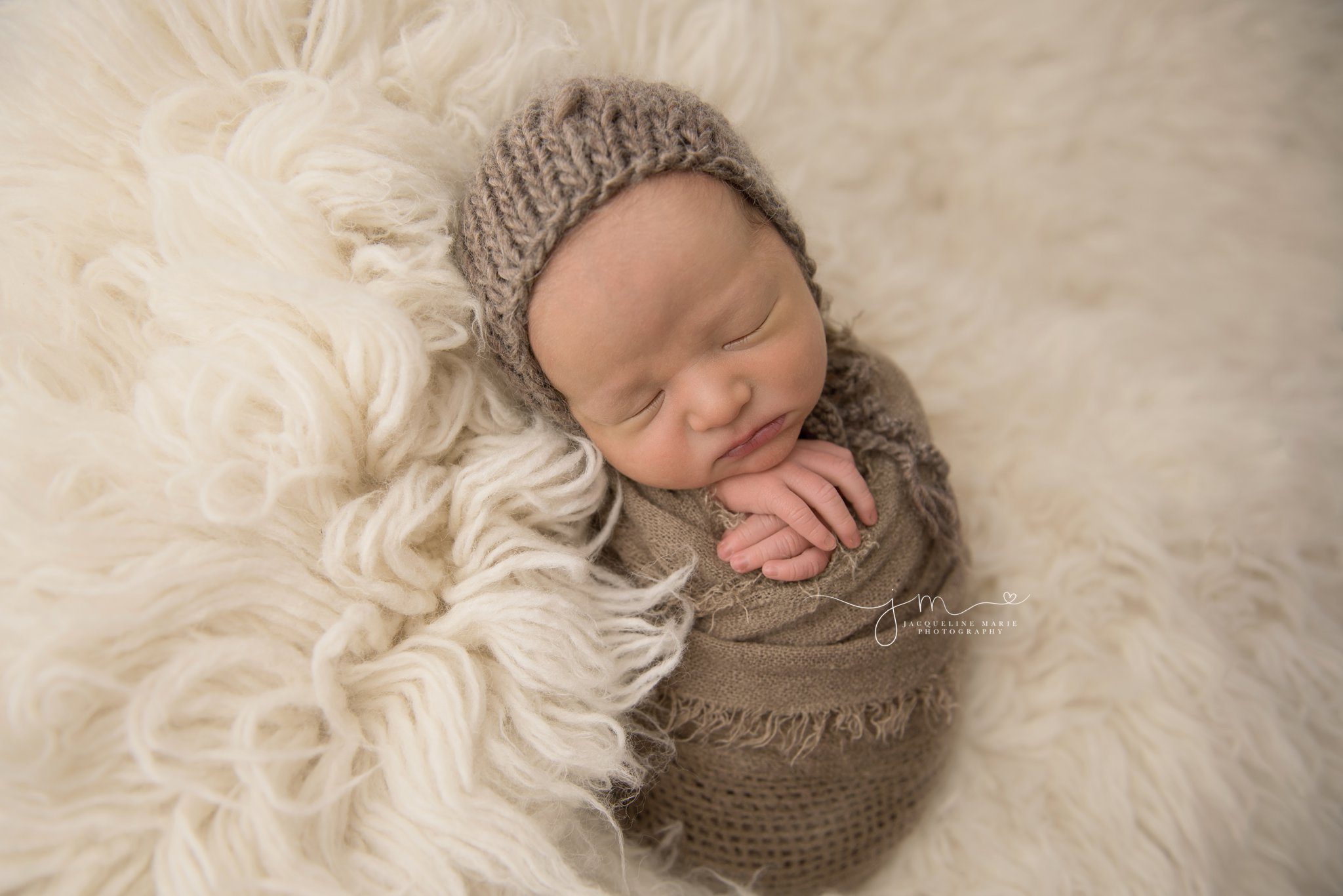 newborn baby boy is sleeping with hands folded for newborn photography session in columbus ohio