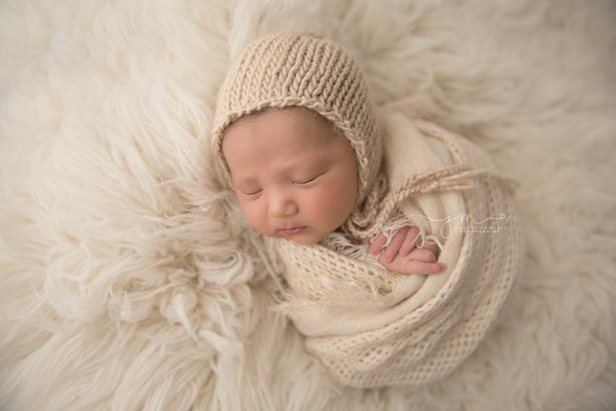 1 week old newborn baby boy is swaddled on a cream fur rug during newborn session at columbus ohio photography studio