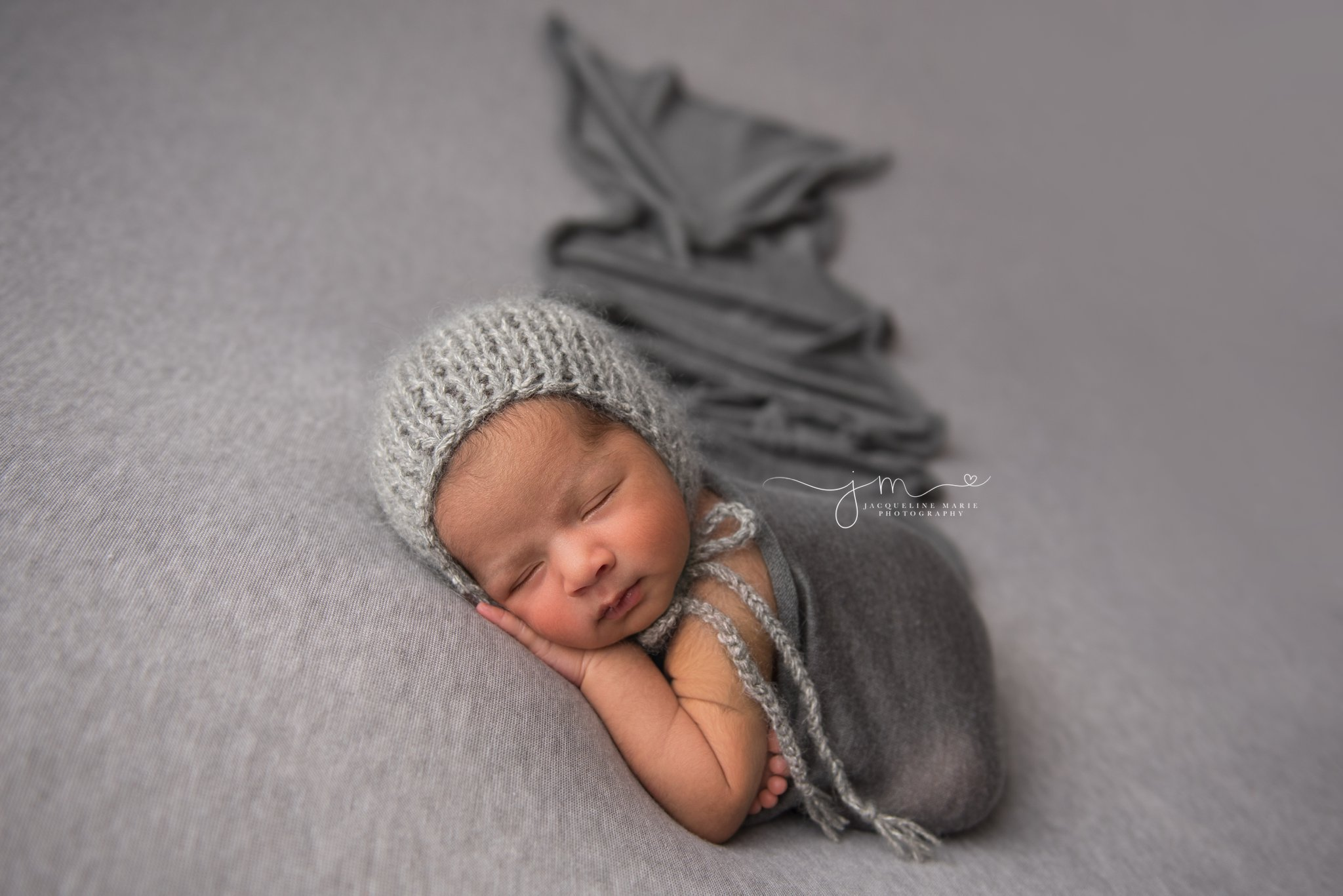 newborn photographer in columbus ohio swaddles baby in dark gray wrap with matching gray bonnet