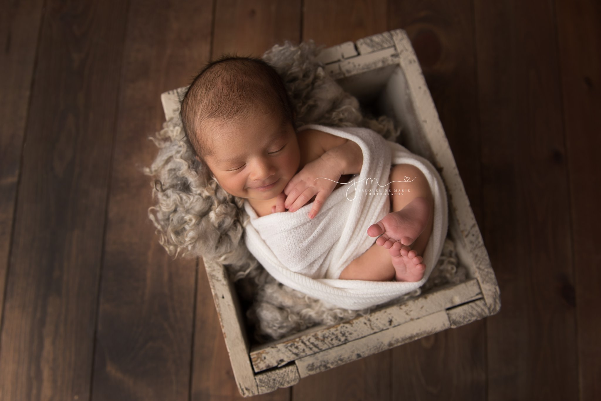 newborn baby boy smiles while swaddled in wood crate during newborn photography session in columbus ohio