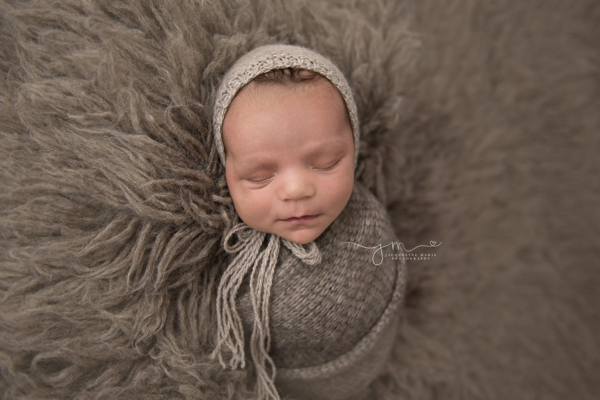 newborn baby boy is swaddled in gray wrap and bonnet on matching float rug in columbus ohio newborn photography studio
