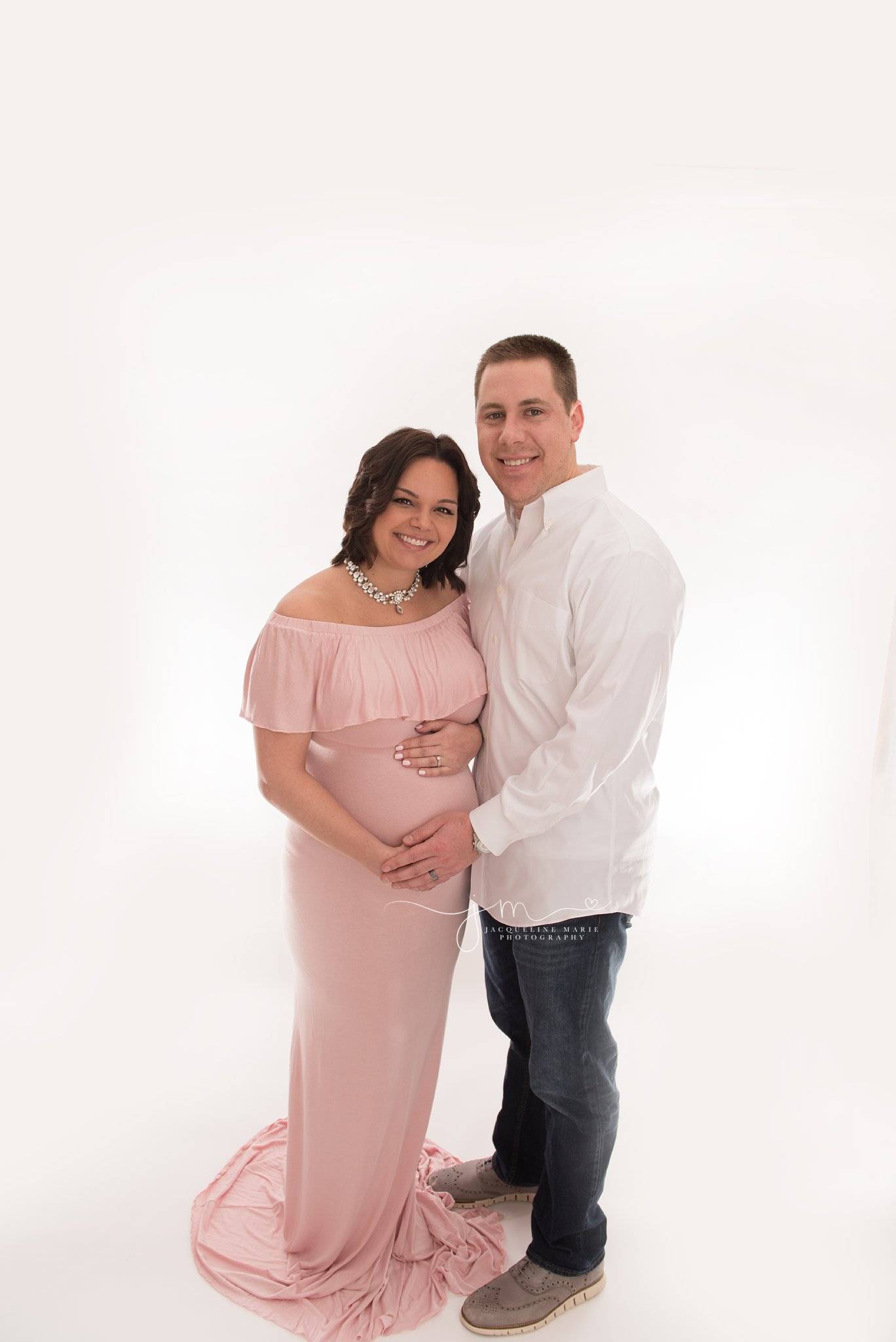 soon to be parents smile with happiness as in columbus ohio photography studio for maternity pictures