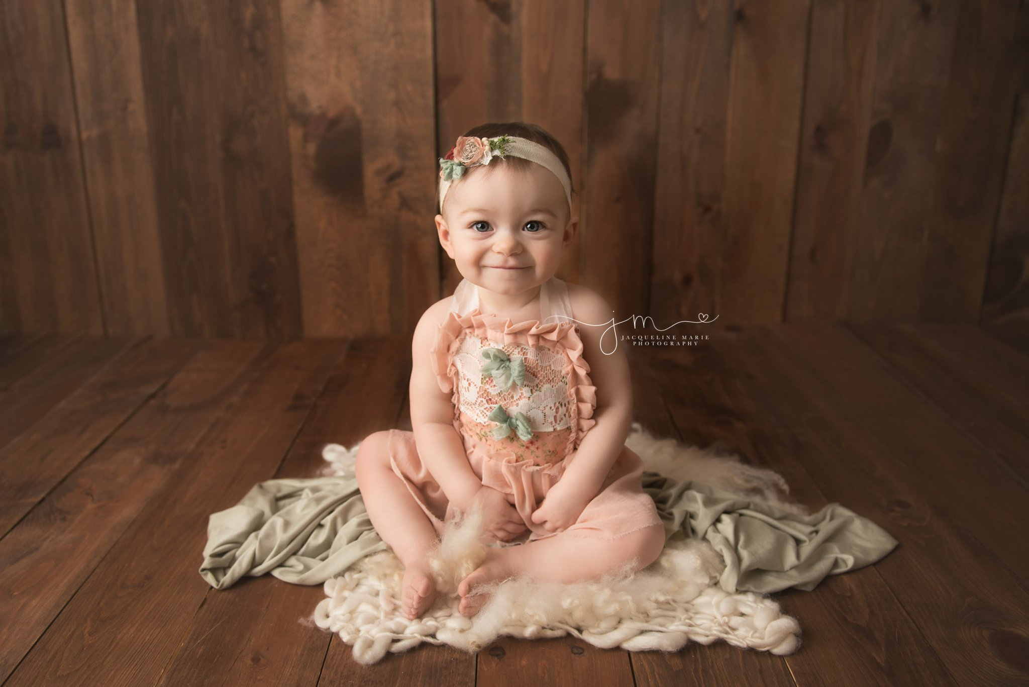 1 year old girl wears peach floral romper for first birthday pictures in columbus ohio
