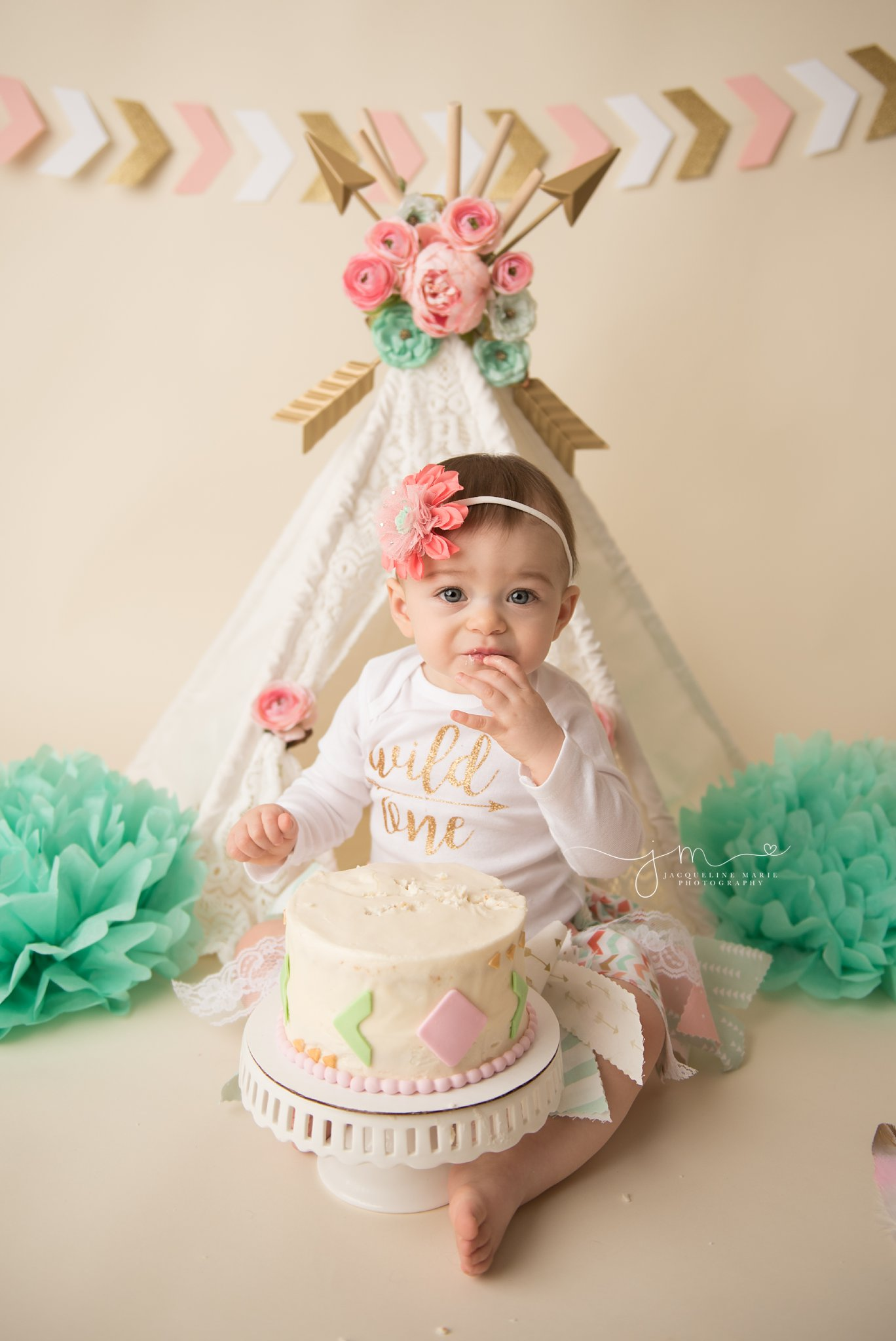 1 year old baby girl eats cake for her first birthday cake smash session in columbus ohio