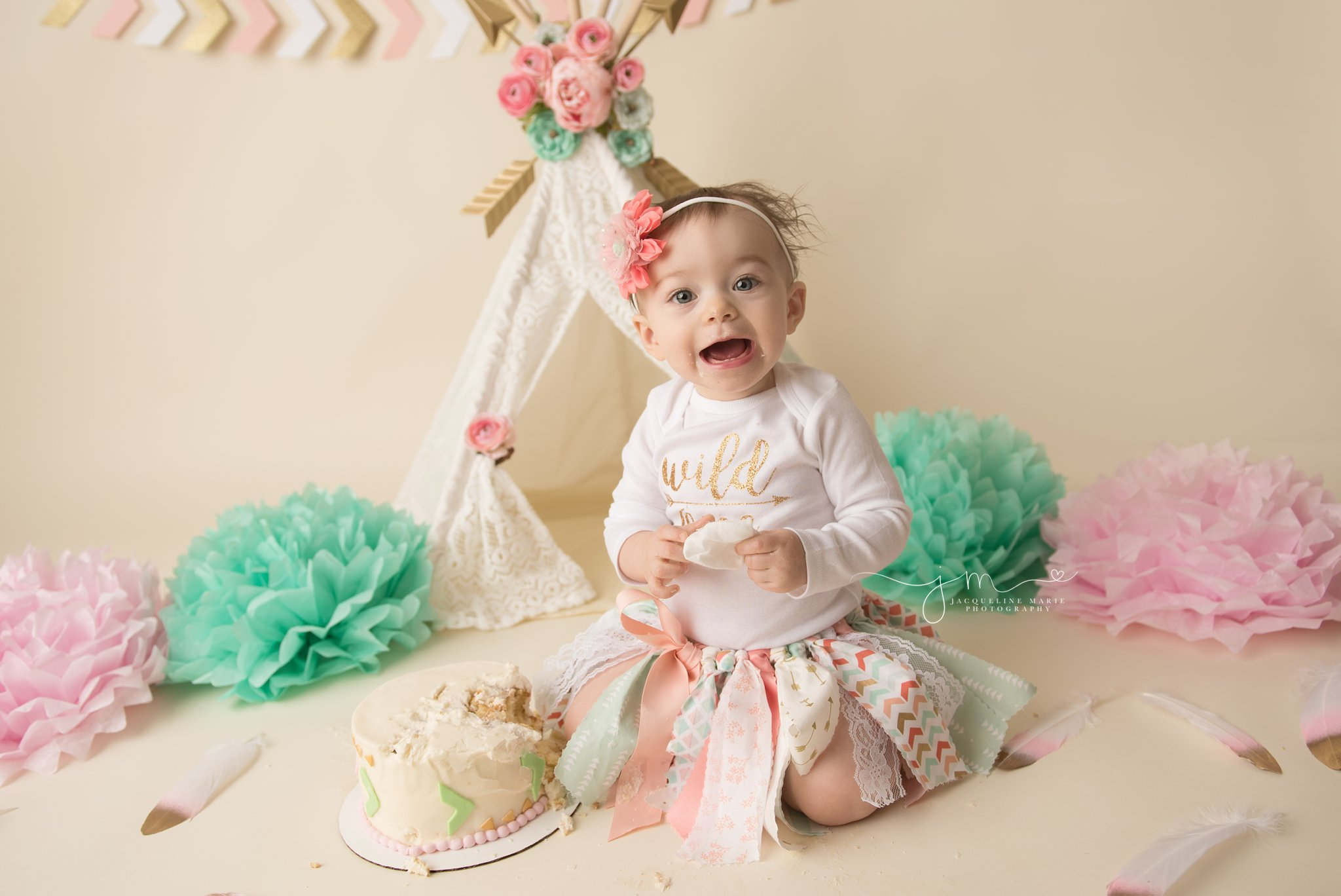 1 year old baby girl enjoyed her cake smash and put icing in her hair in columbus ohio for her first birthday cake smash session