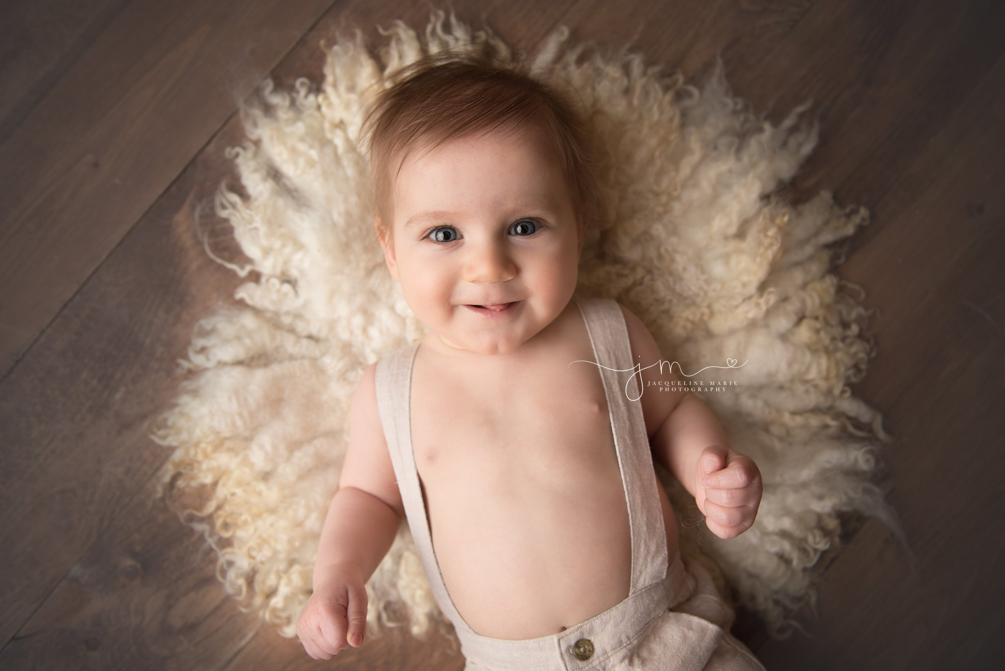 columbus ohio baby photographer features image of baby boy smiling and laying on cream wool curly layer in portrait studio for milestone session