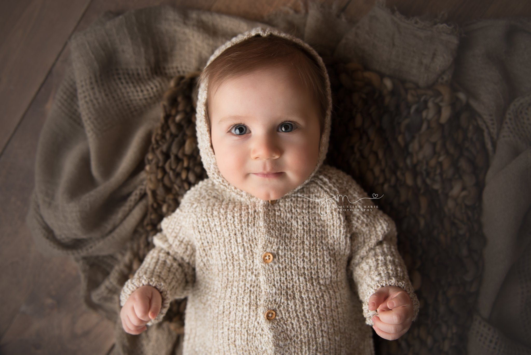 columbus ohio 6 month old baby boys wears hooded sweater at photography studio for milestone pictures